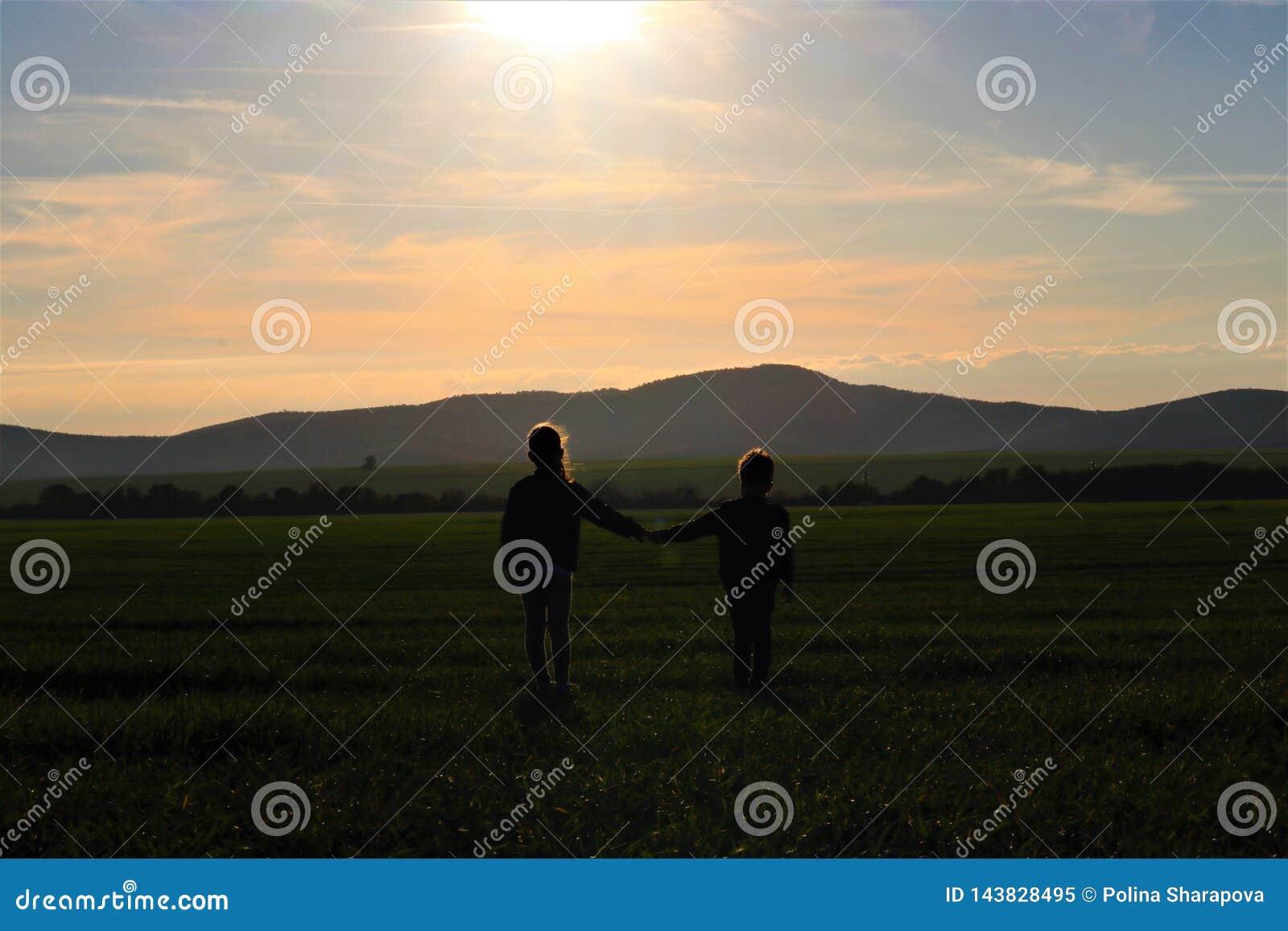 De silhouetten van twee kleine kinderen letten op de mooie zonsondergang