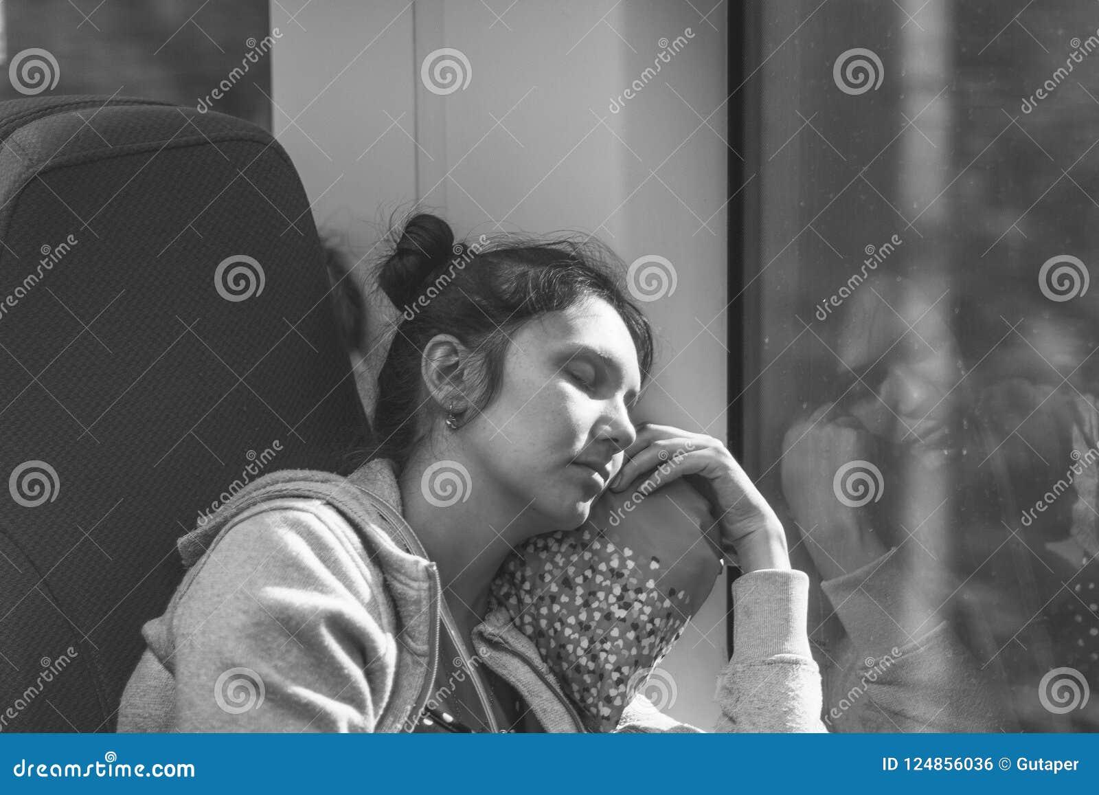 De slaap jonge vrouw die in hoge snelheids elektrische trein Lastochka berijden in de zomer, zwart-witte foto