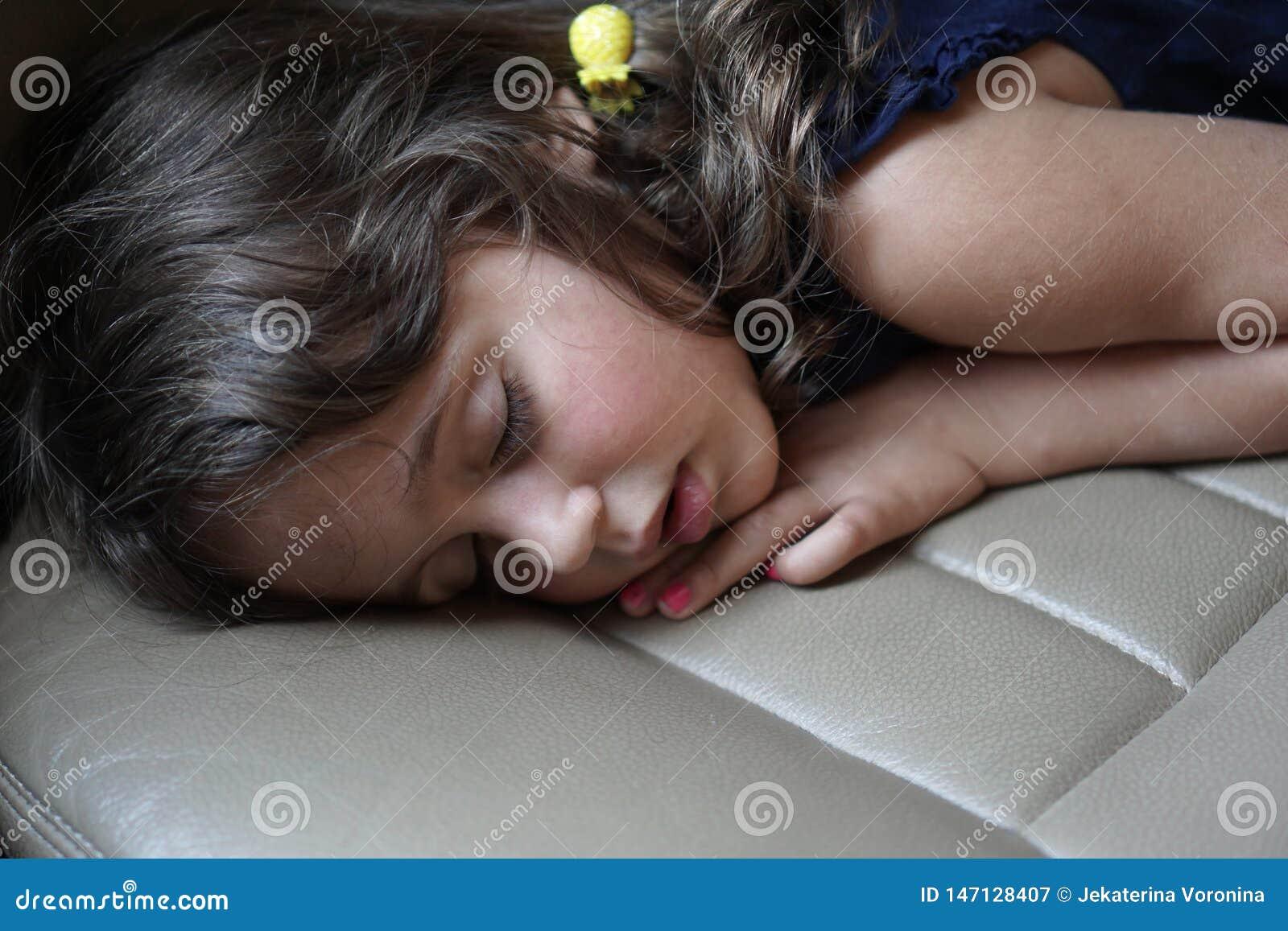 De slaap van het 3-4 éénjarigenmeisje in de achterbank van de auto