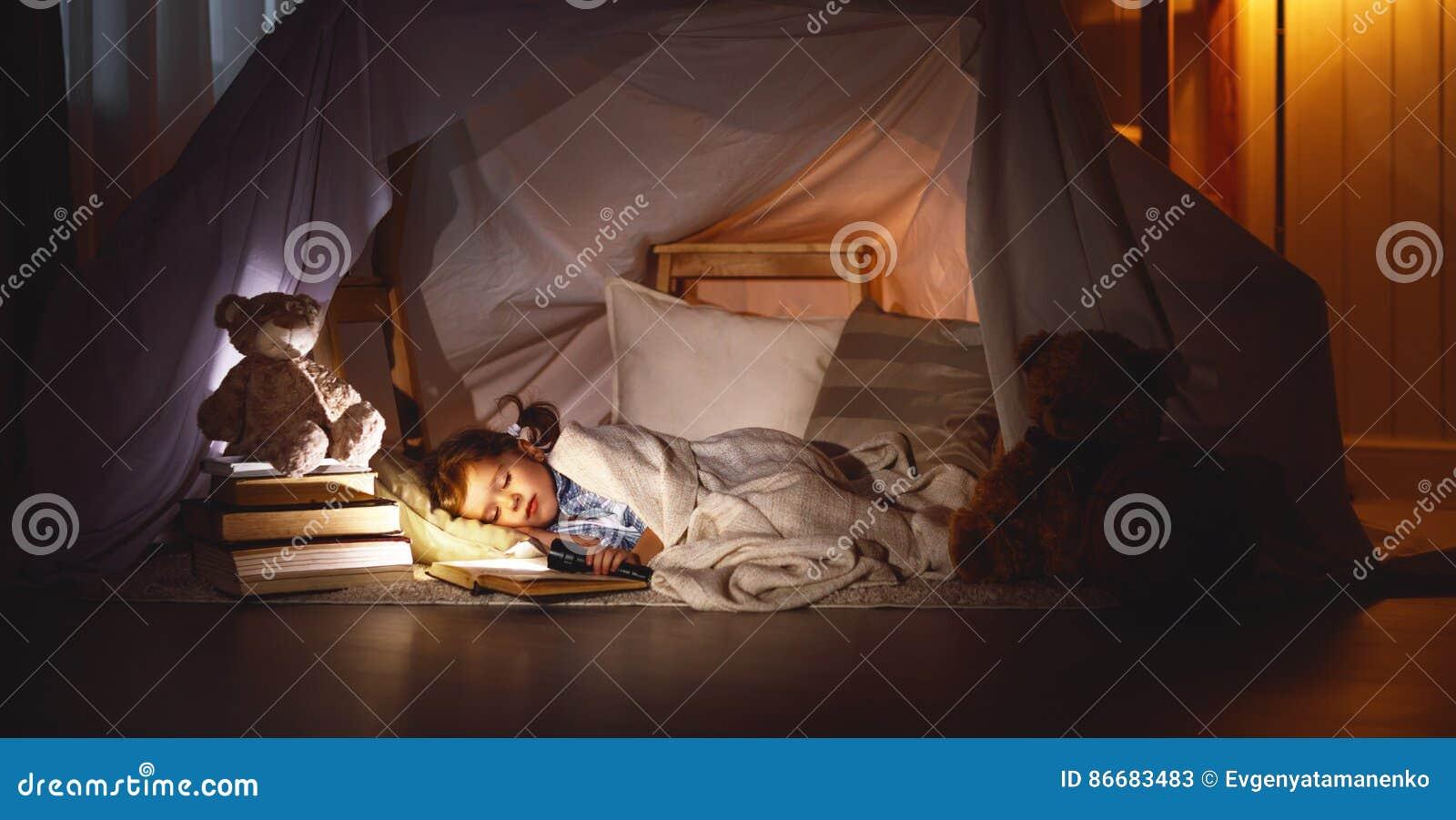 De slaap van het kindmeisje in tent met boek en flitslicht