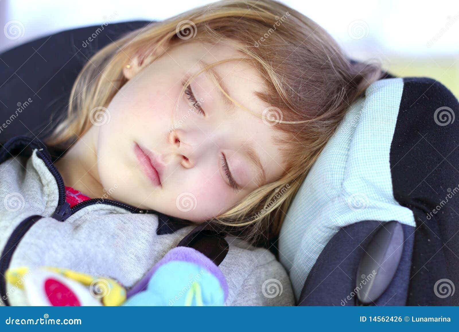 De slaap van het meisje op de veiligheidszetel van de kinderenauto