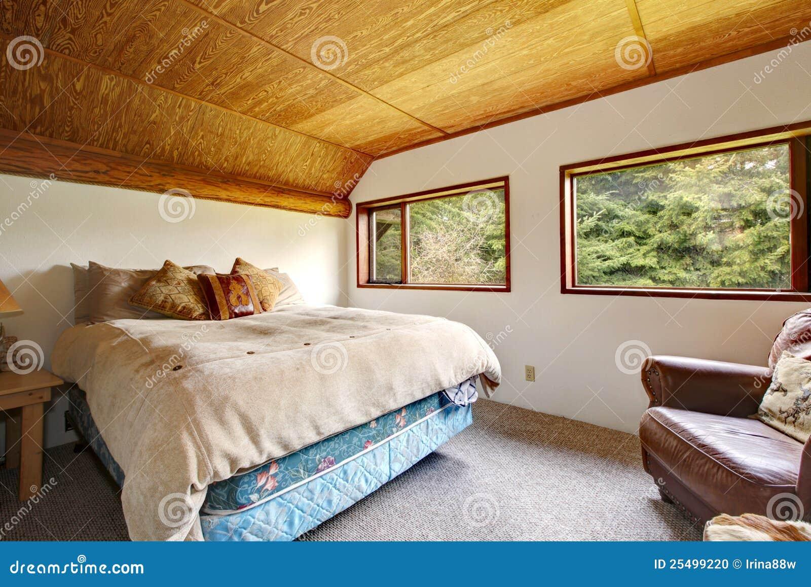 De slaapkamer van de cowboy met houten plafond en houten mening ...