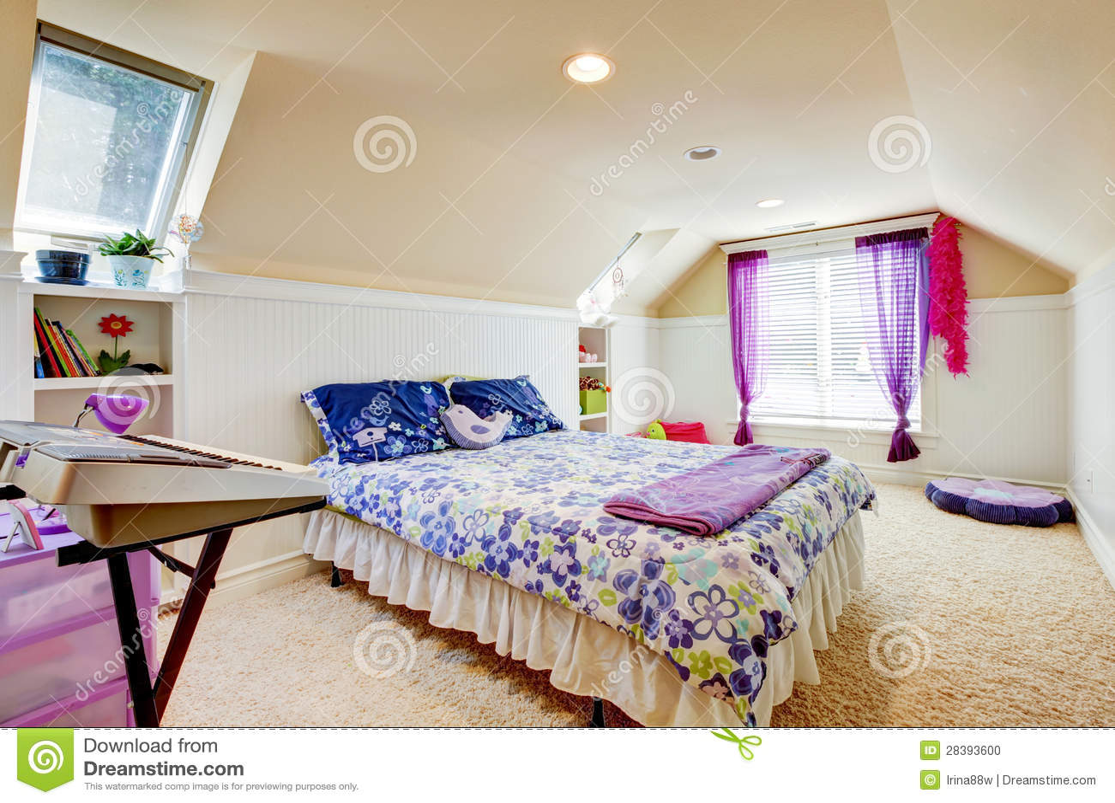 de slaapkamer van het meisje met zolderplafond en beige tapijt met speelgoed stock foto