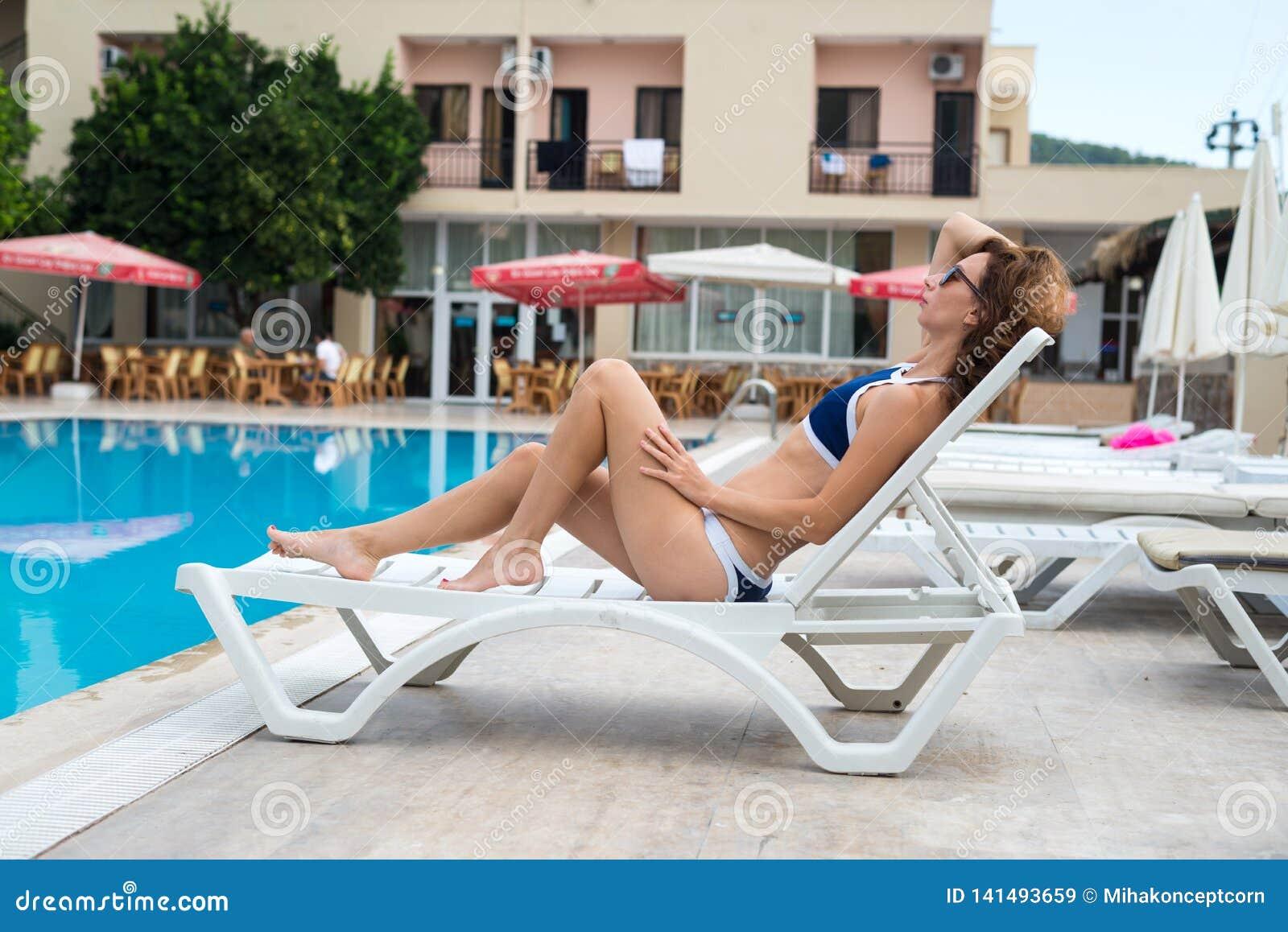 De slanke jonge vrouw in een bikini zonnebaadt dichtbij de pool Een vrouw ligt op een ligstoel