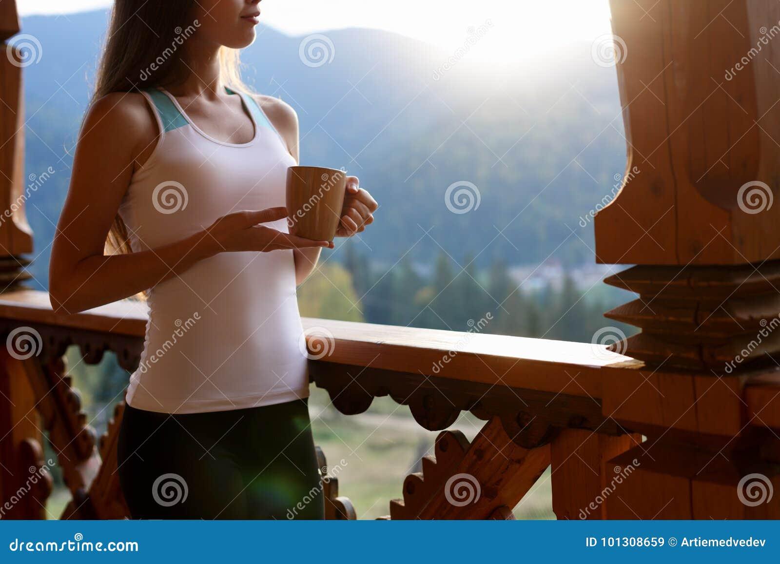 De slanke Kaukasische vrouw houdt kop thee in haar handen bij bergtoevlucht Sportenmeisje met hete koffiemok bij houten balkon