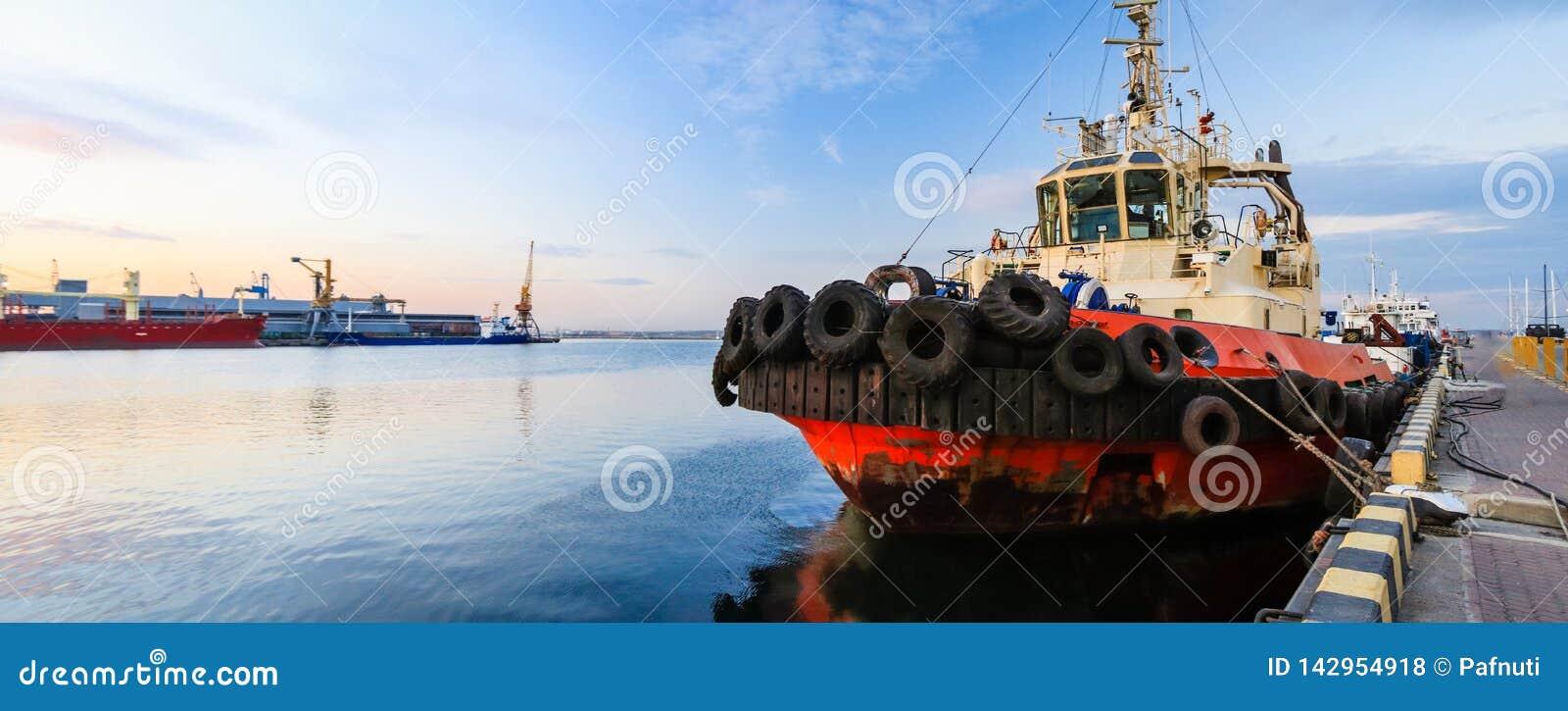 De sleepboot is bij de pijler in de zeehaven