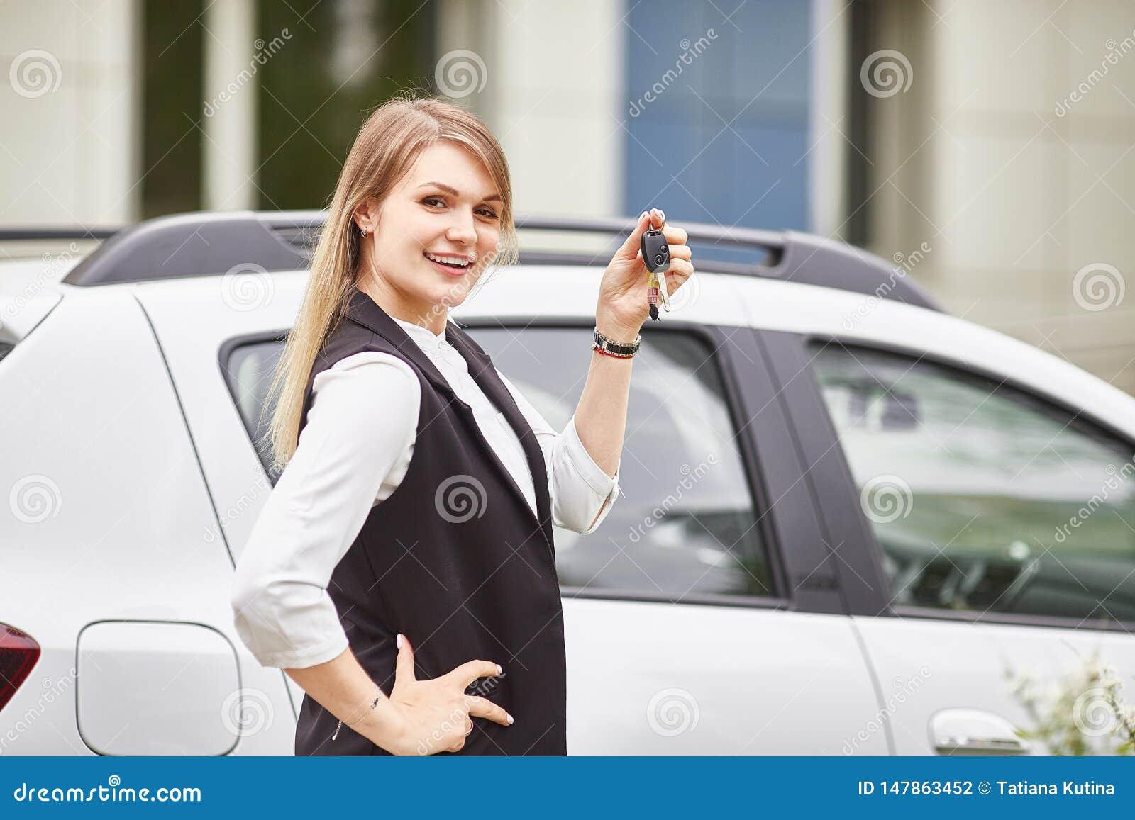 De sleutels van de vrouwenholding tot nieuwe autoauto en het glimlachen bij camera