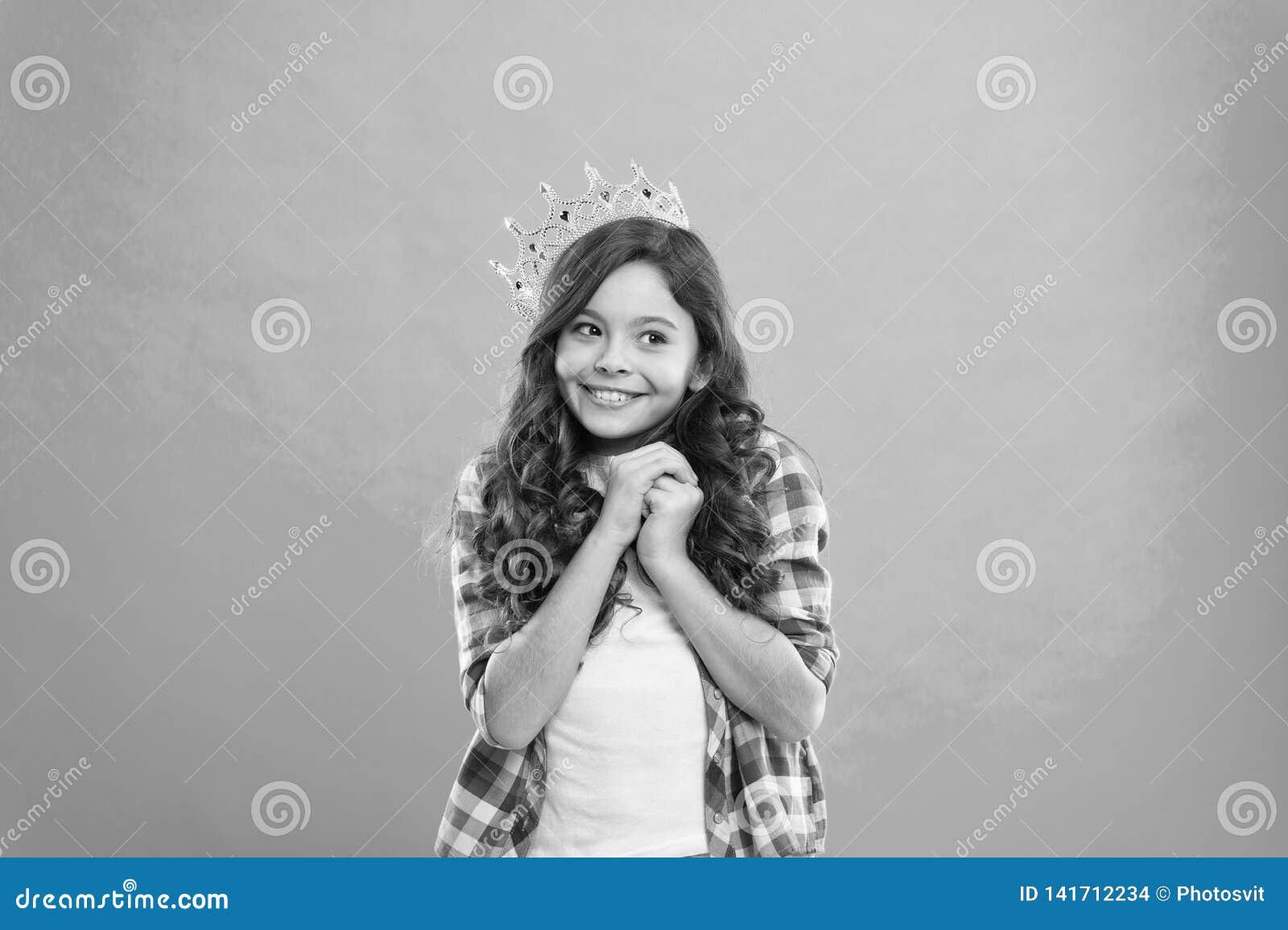 De slijtagekroon van de meisjes leuke baby terwijl tribune blauwe achtergrond Geworden prinsesconcept Elk meisje die prinses drom