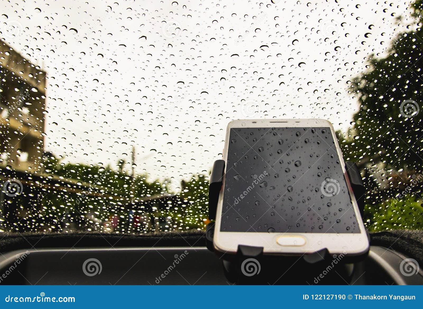 De slimme telefoon is off-line met regendruppelsachtergrond, die op de regenachtige dag in de auto werken