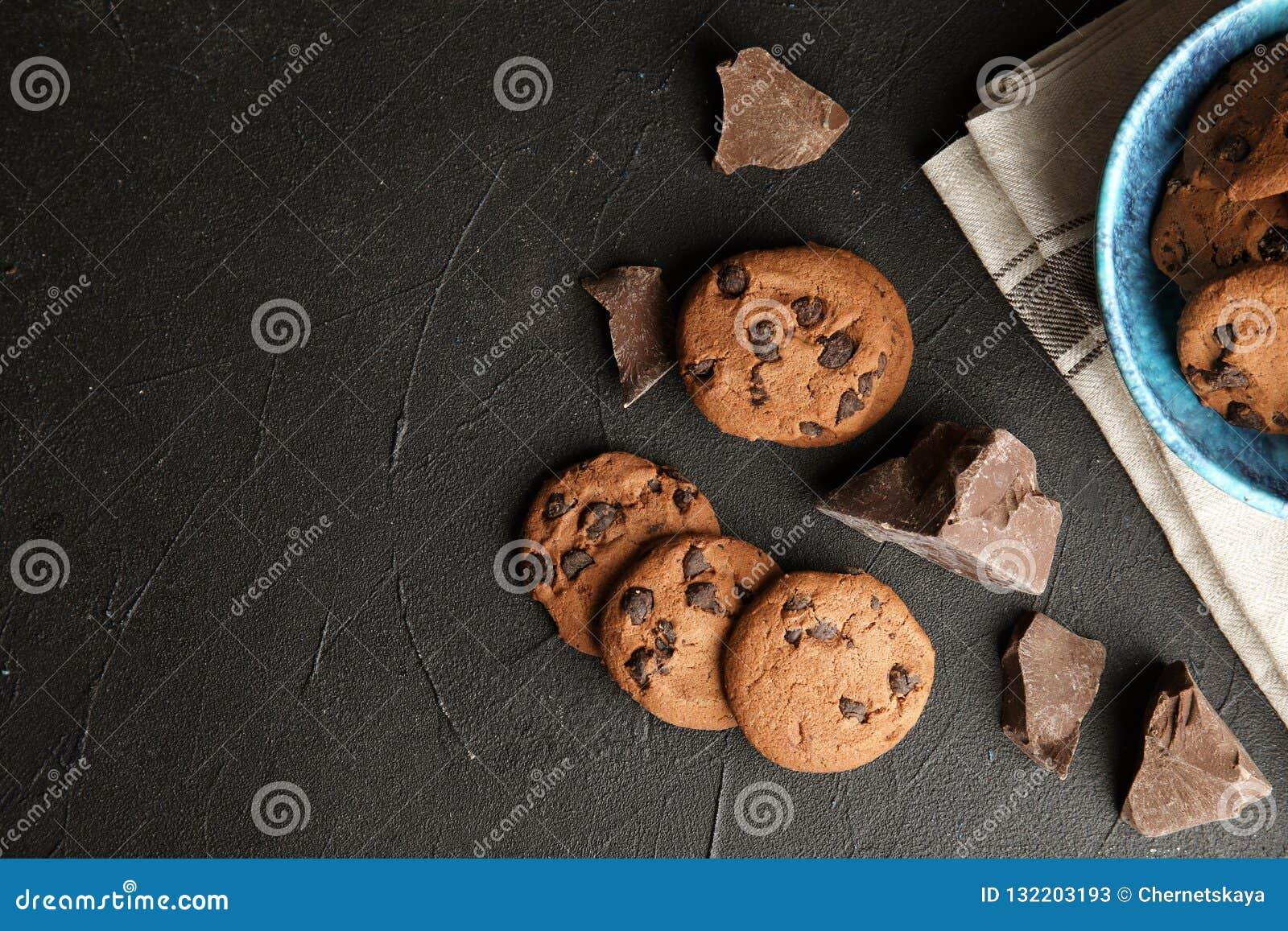 De smakelijke chocoladeschilferkoekjes op donkere vlakke achtergrond, leggen