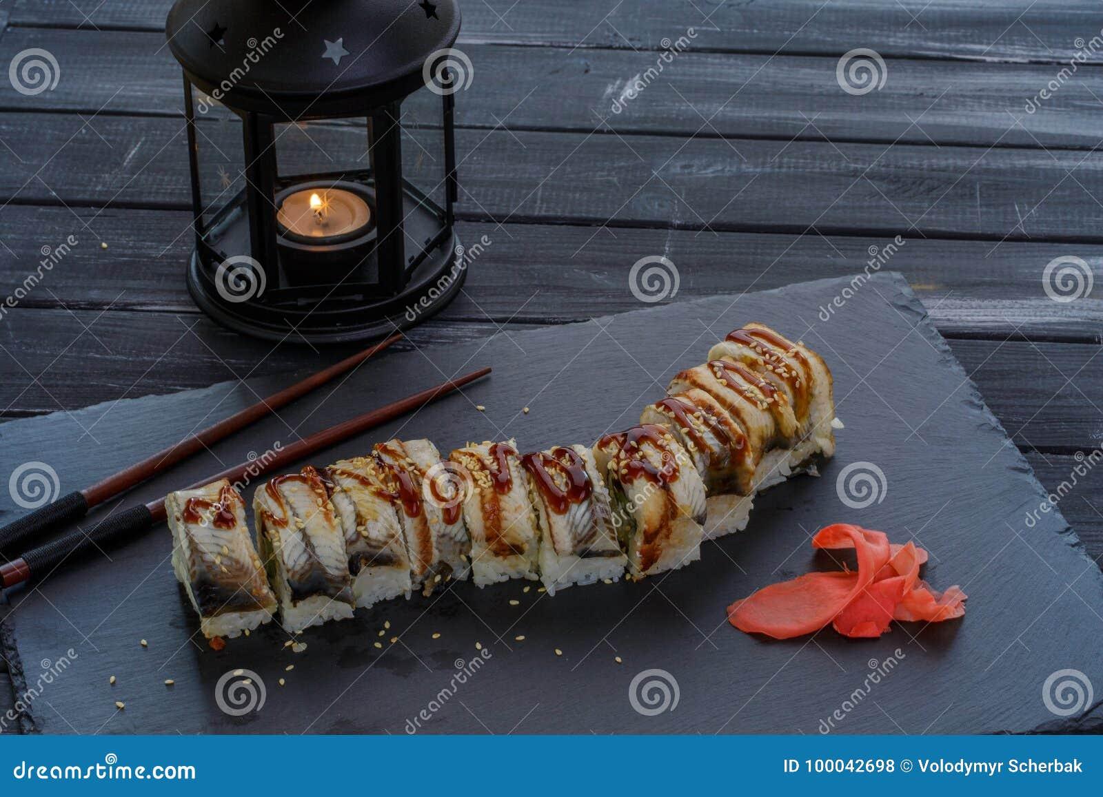 De smakelijke en heerlijke traditionele Japanse sushi rollen met zeevruchten en palingsvissen op zwarte achtergrond met kaars