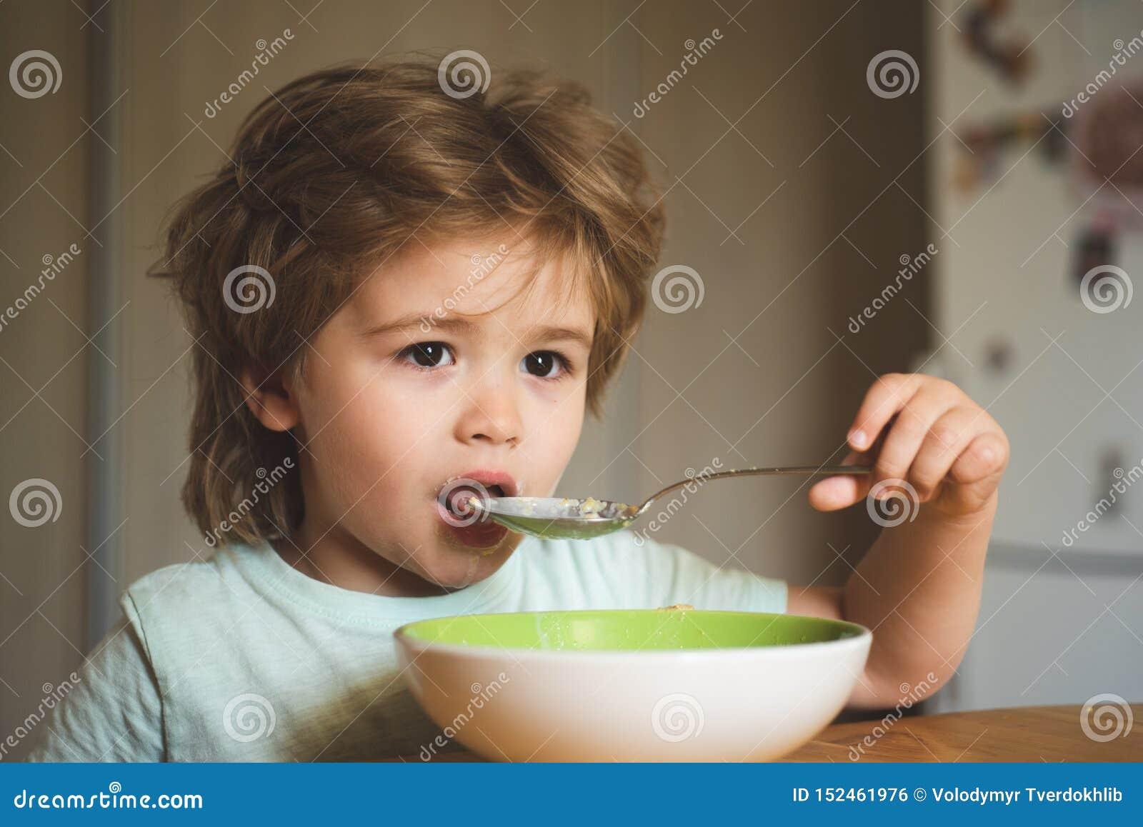 De smakelijke jonge geitjes ontbijten Leuk kind die ontbijt thuis eten Baby het eten Goedemorgen in Gelukkige familie Hongerig we