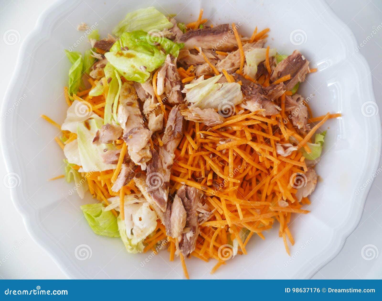 De smakelijke salade met sla, tonijnvissen, sneed wortelen †‹â€ ‹, linnenzaden, olijfolie en balsemieke azijn op een witte cera