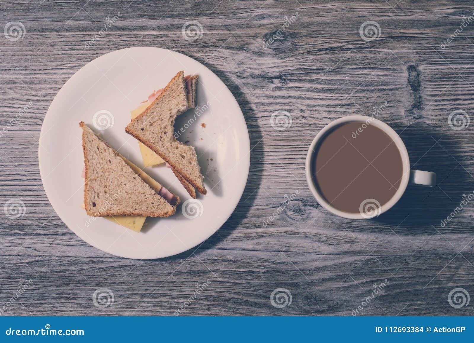 De snackrust ontspant uit koel snel voedsel etend concept van de troep het ongezonde voeding Op het Werk Gebeten kaassandwich met