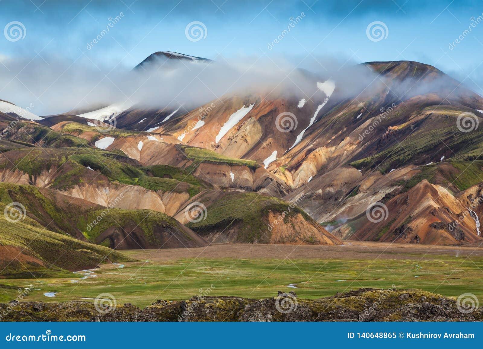 De sneeuw ligt in de holten van multicolored bergen