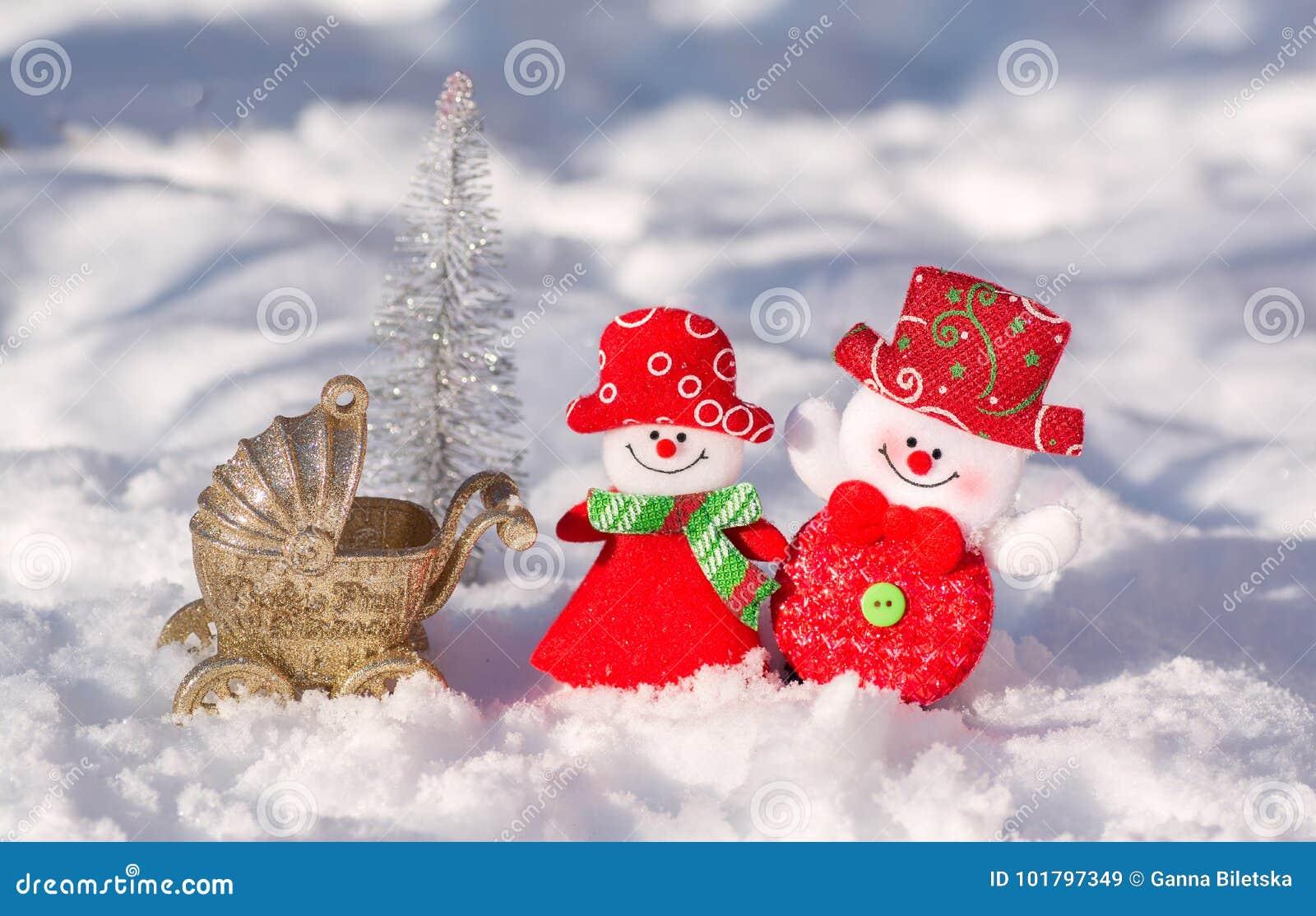 De de sneeuwmanechtgenoot en vrouw zijn prachtig gekleed glimlachend tegen de achtergrond van een glanzende Kerstboom met een wan