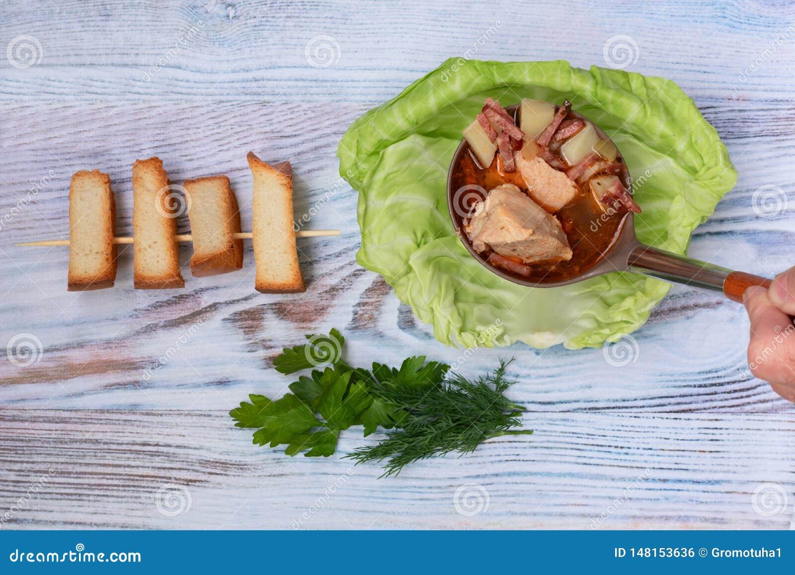 De soep in vleesbouillon wordt gekookt met wordt verse kruiden en croutons gegoten in een plaat met koolblad dat