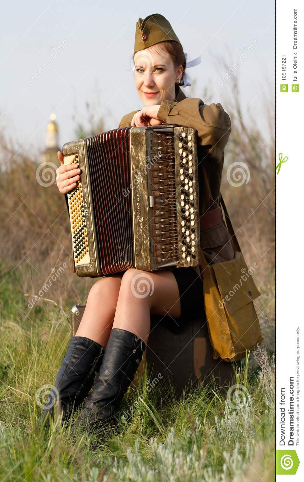 De sovjet vrouwelijke militair in eenvormig van Wereldoorlog II zit met een harmonika op een koffer