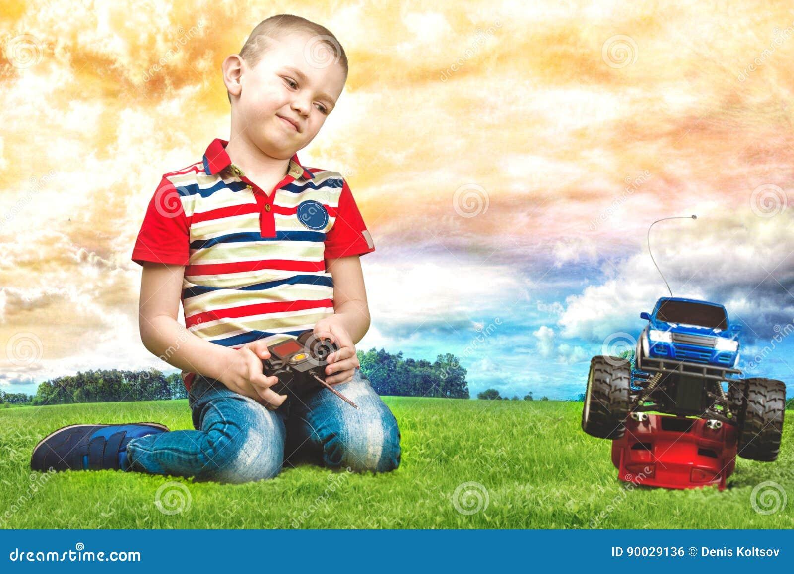 De spelen van de babyjongen met de auto op de afstandsbediening Het zitten op het groene gazon