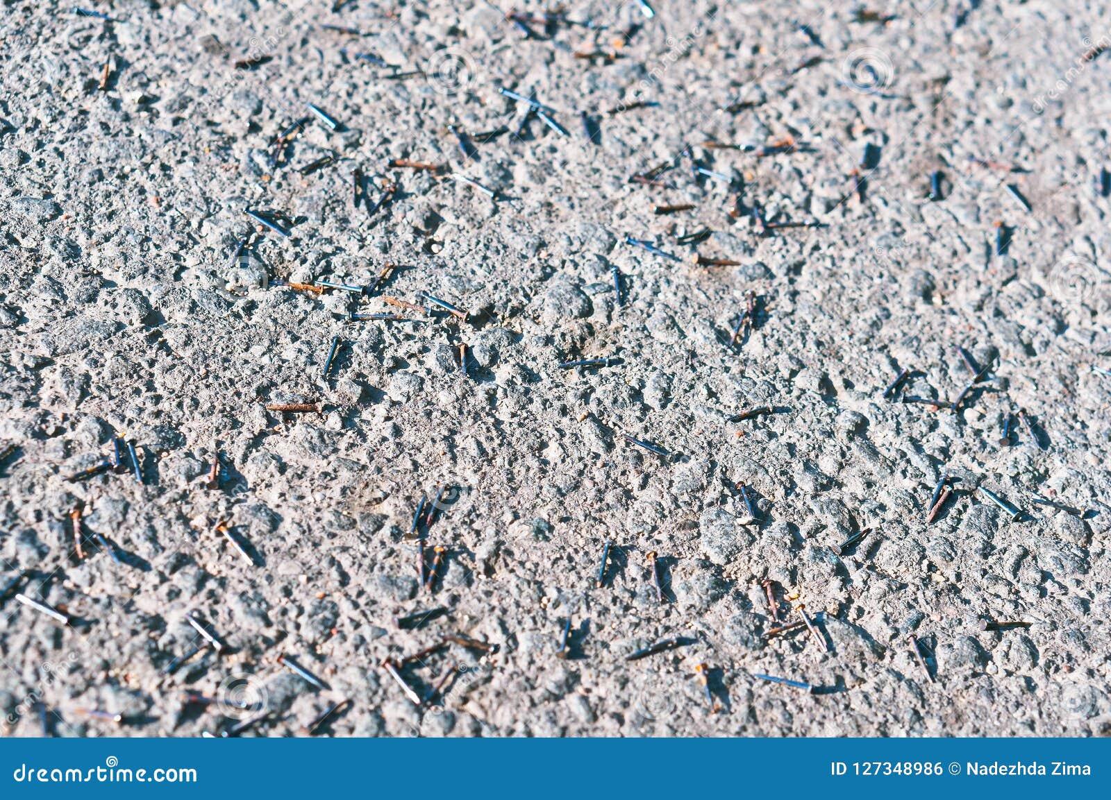 De spijkers van het bouwmetaal verspreidden zich op de weg, kleine ijzerspijkers op de weg