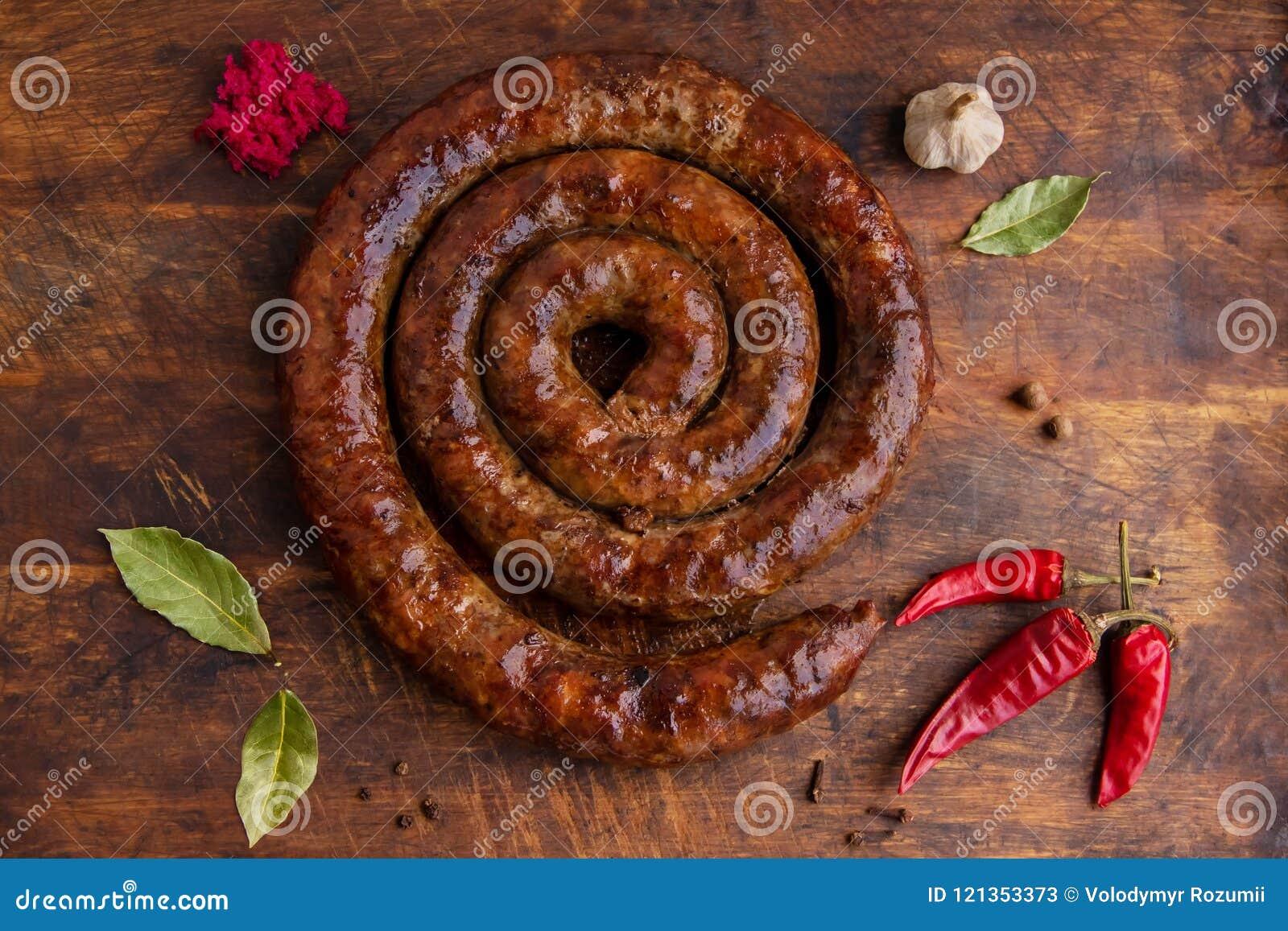 De spiraalvormige die worstring in een oude oven wordt gebakken is op een houten raad met peper en knoflook