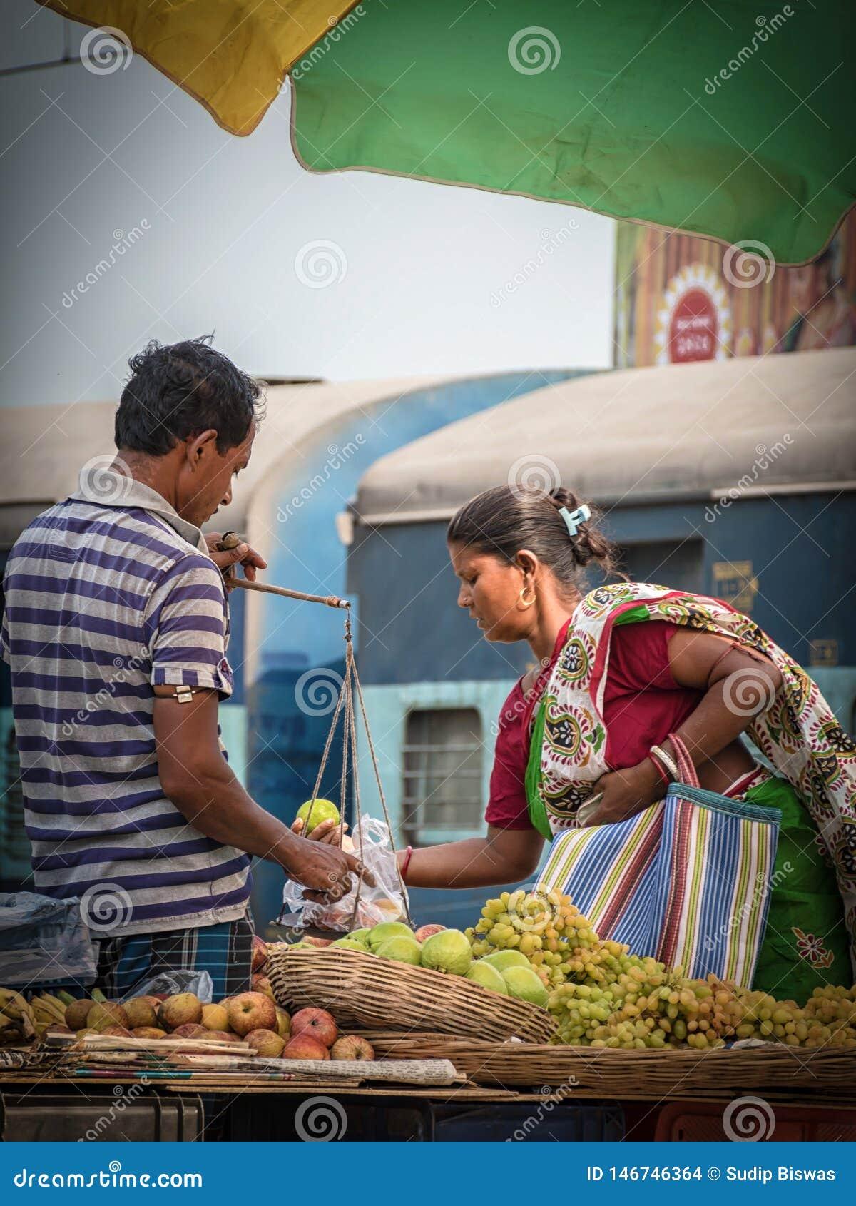 De spoorwegverkoper verkoopt vruchten aan de reizigers