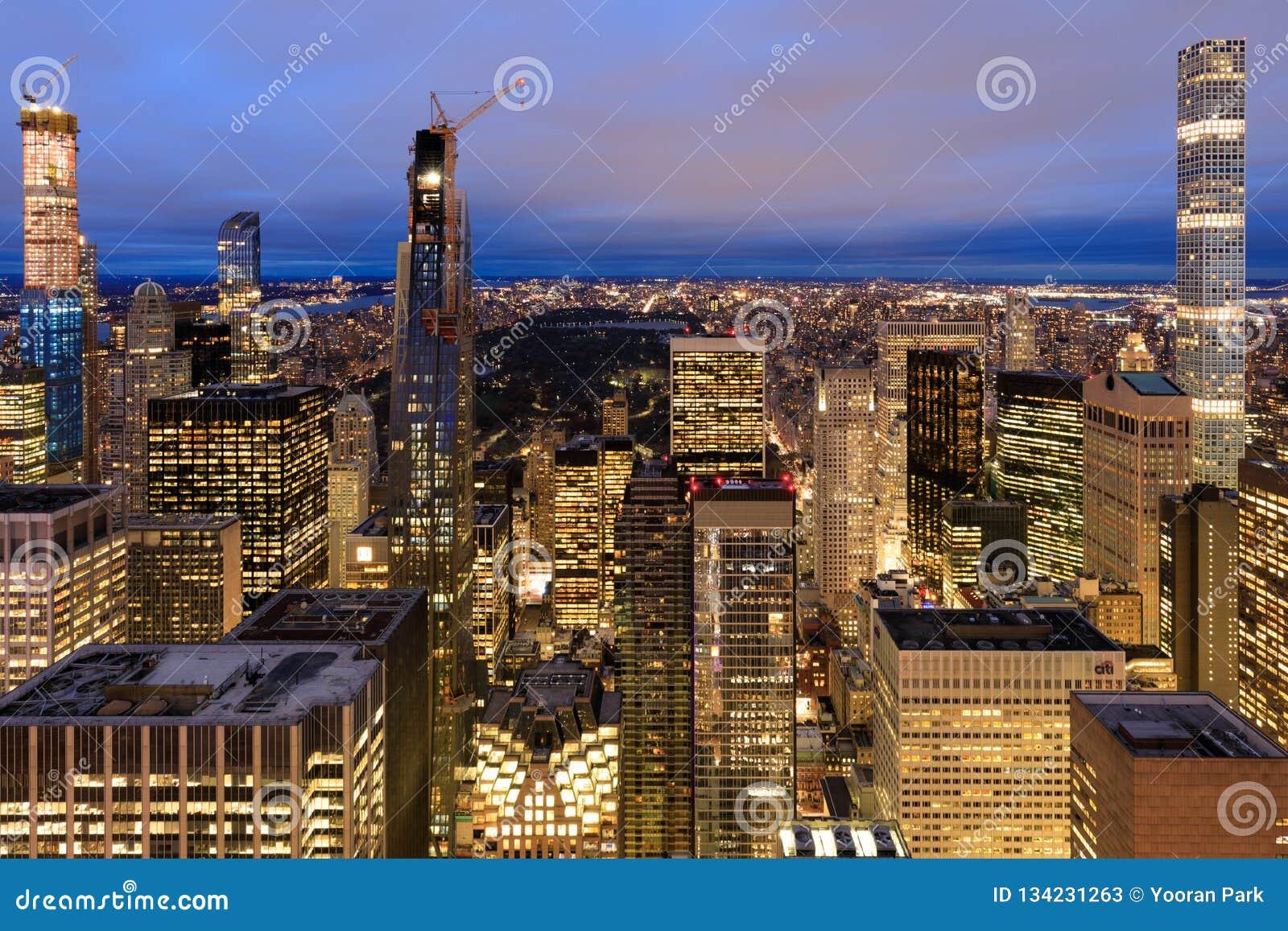 De Stadshorizon van New York met stedelijke wolkenkrabbers bij nacht