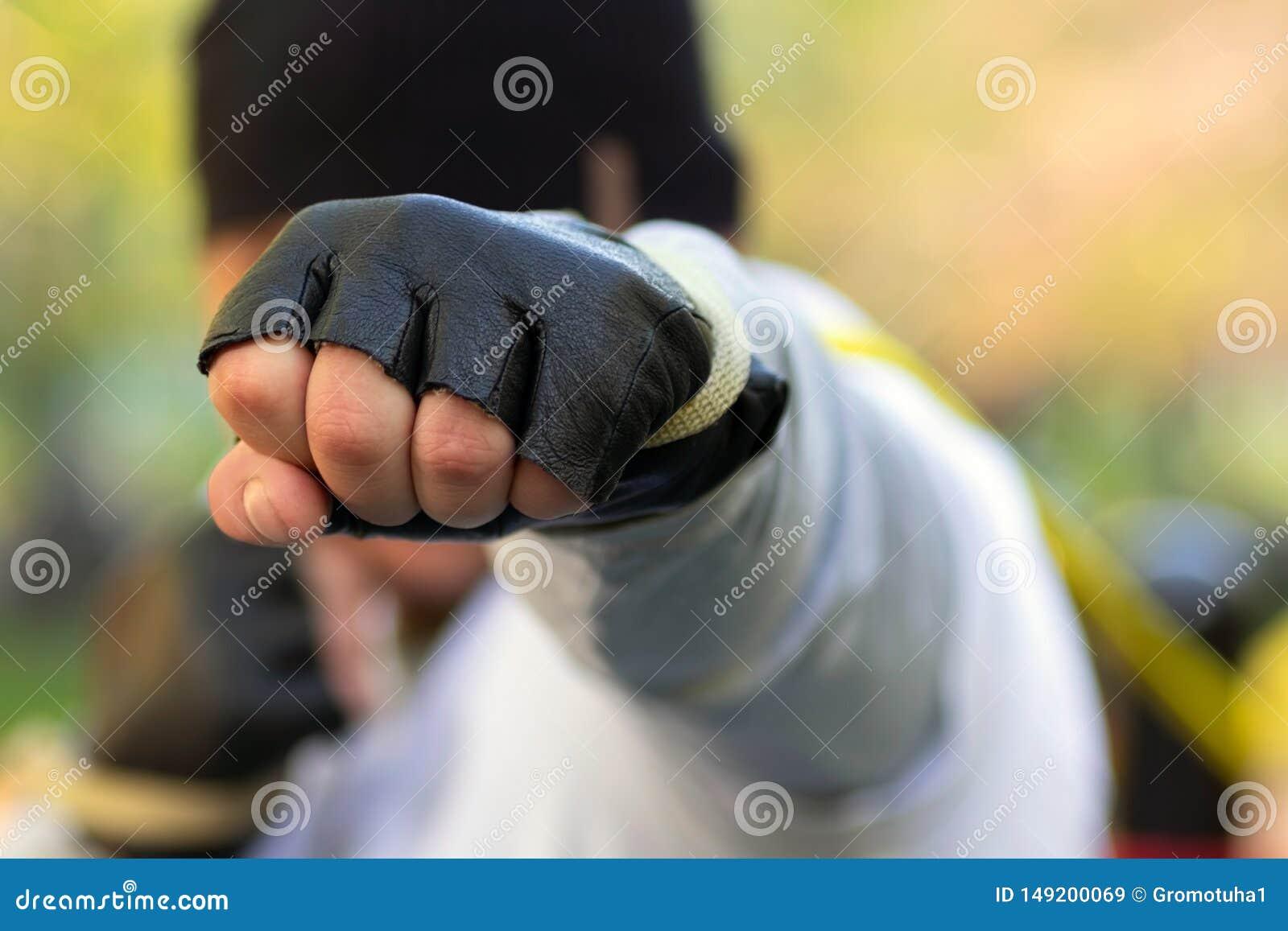 De stakingen van de boksermens met zijn vuist in een beschermende handschoen bij het doel In zijn die vuist met groot rubber van