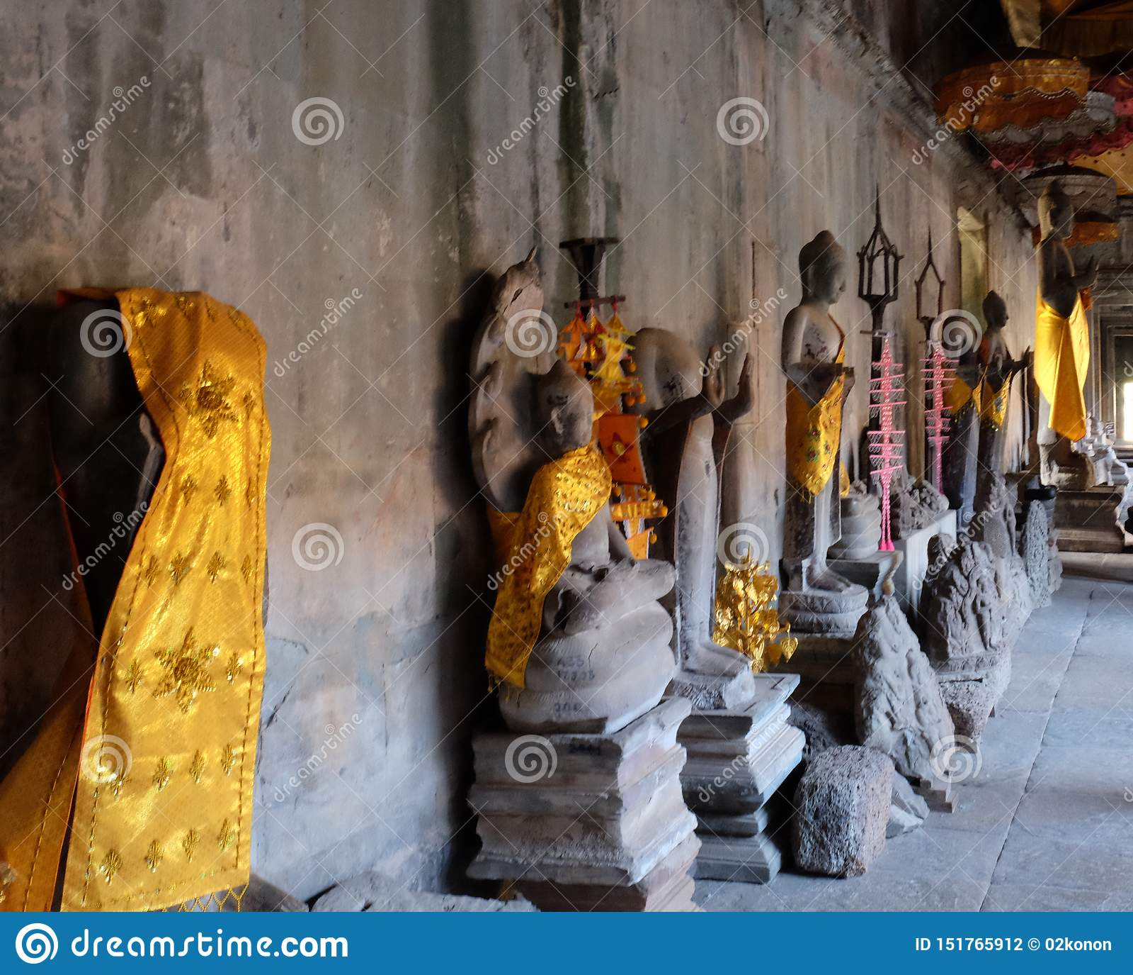 De standbeelden van Boedha in gouden robes bevinden zich langs de muren van een oude tempel Een plaats van godsdienstige verering