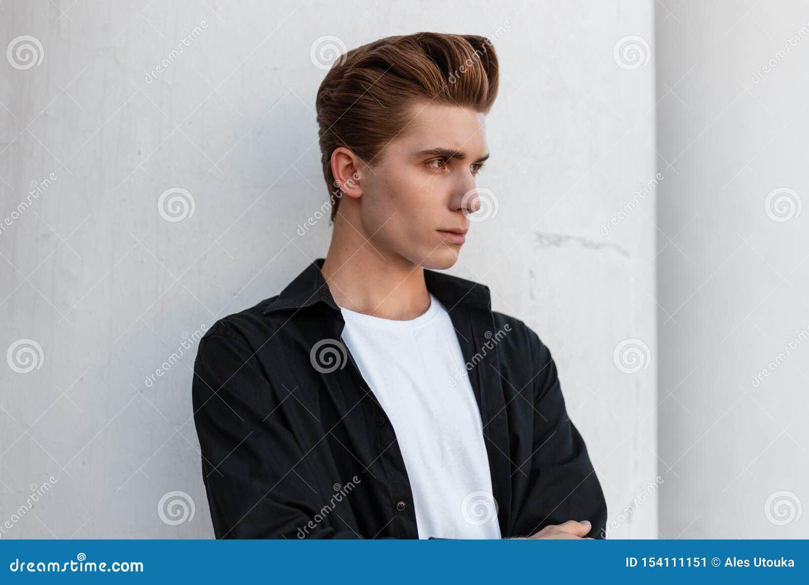 De stedelijke jonge mens met een modieus kapsel in een elegant zwart overhemd in een witte T-shirt bevindt zich dichtbij een uits