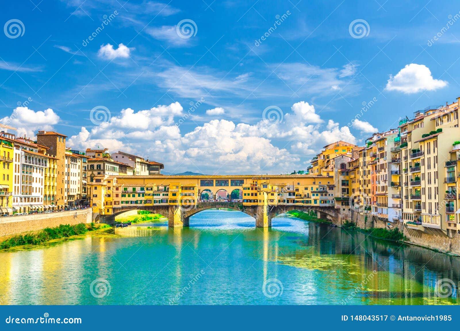 De de steenbrug van Pontevecchio met kleurrijke gebouwenhuizen over het blauwe turkooise water van Arno River en de dijk wandelen