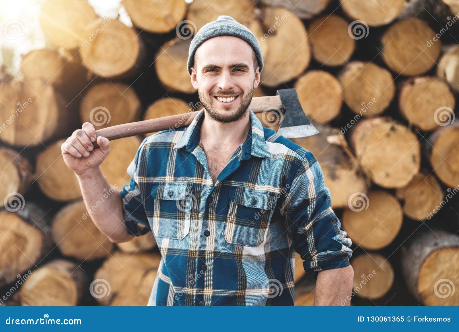 De sterke gebaarde houthakker die plaidoverhemd dragen houdt bijl op zijn schouder