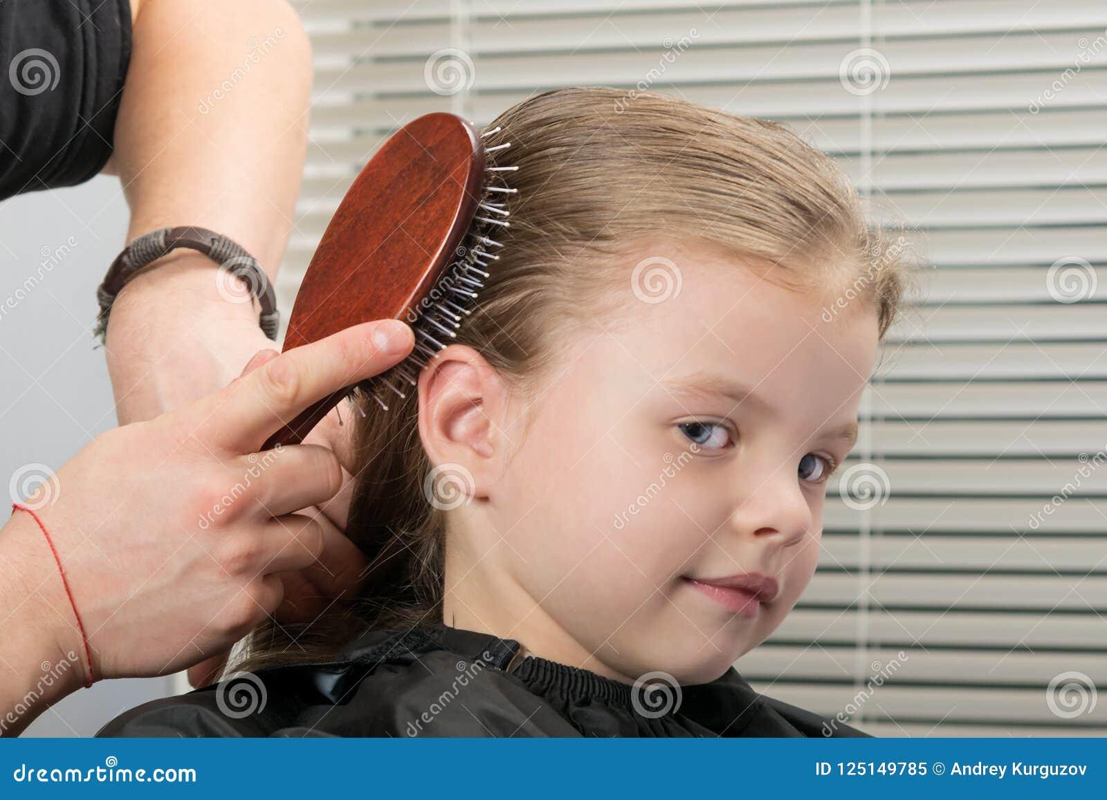 De stilist maakt haar het stileren op het hoofd met een kam voor een weinig glimlachend meisje