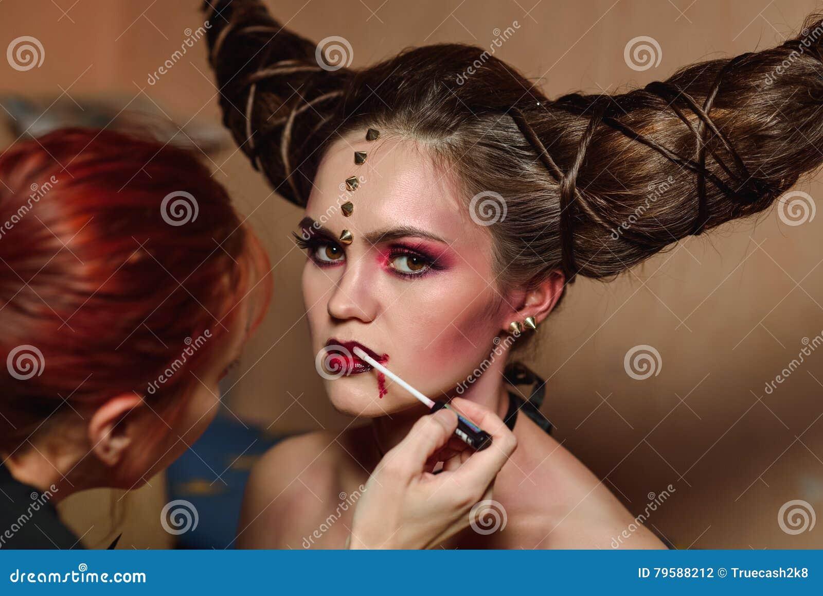 De stilist maakt Halloween-make-up, borstelend bloed op modellenlippen