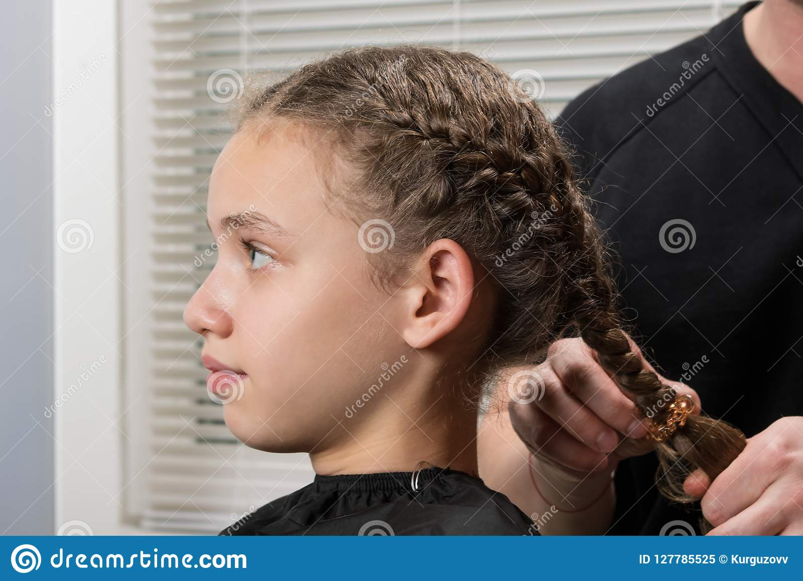 De stilist maakt het meisje tot een haarvlecht, close-up