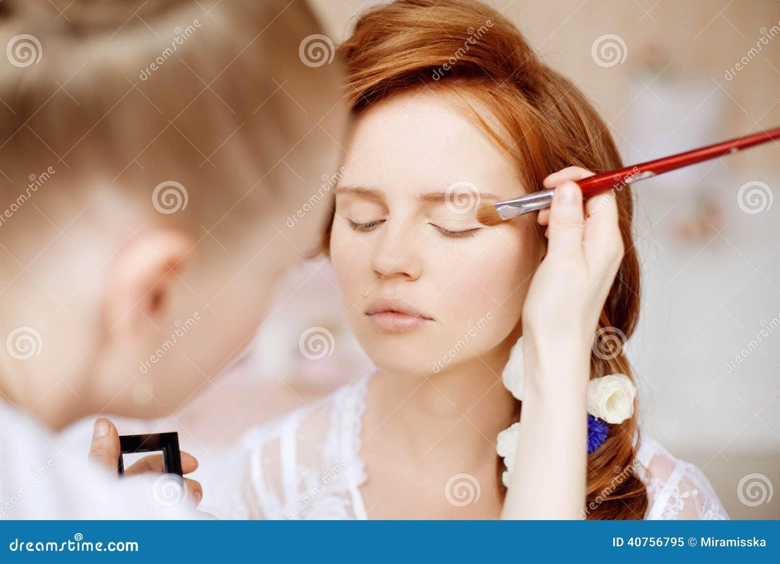 De stilist maakt make-upbruid vóór het huwelijk