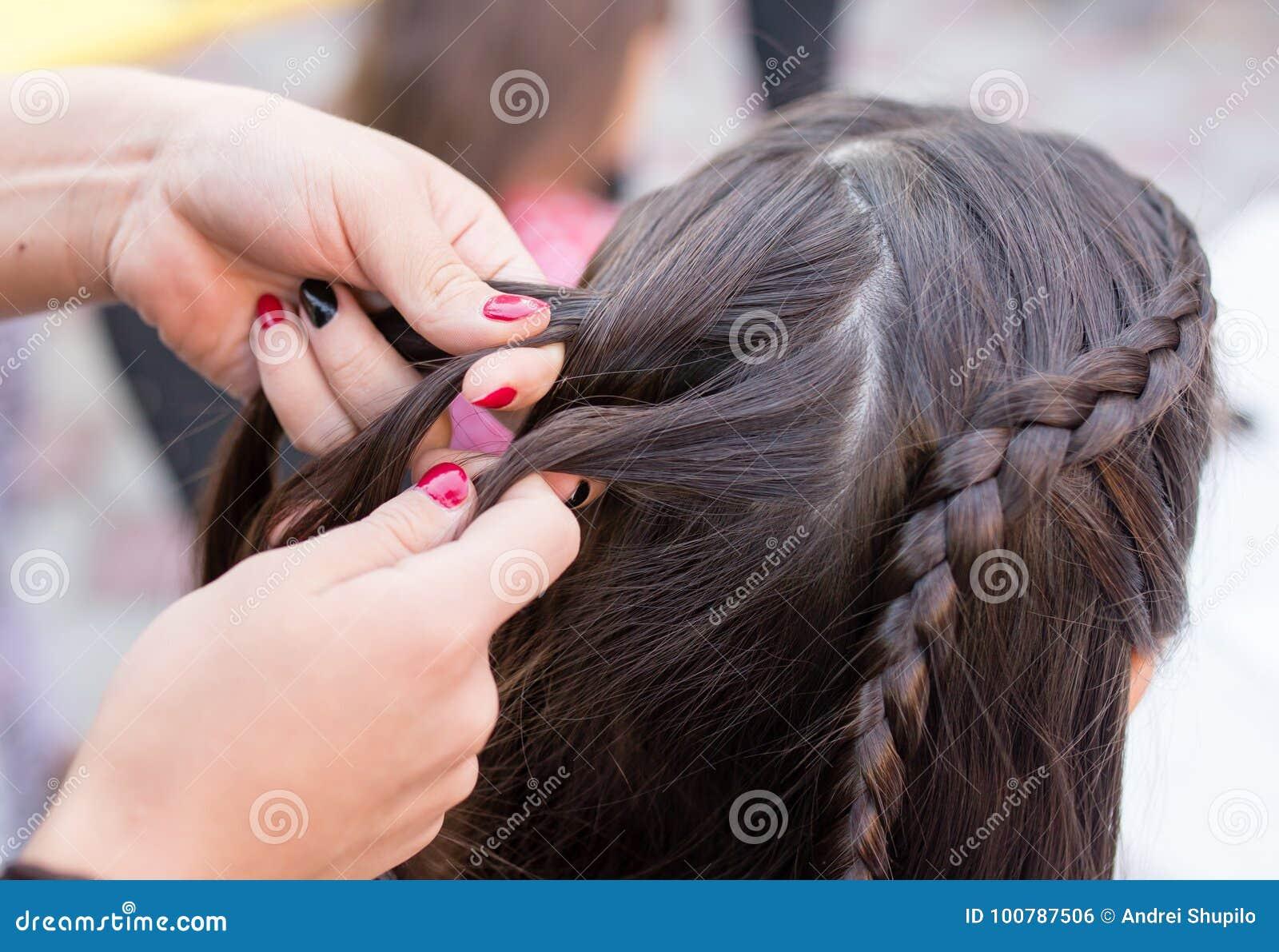 De stilist weeft de vrouwelijke vlechten op het hoofd