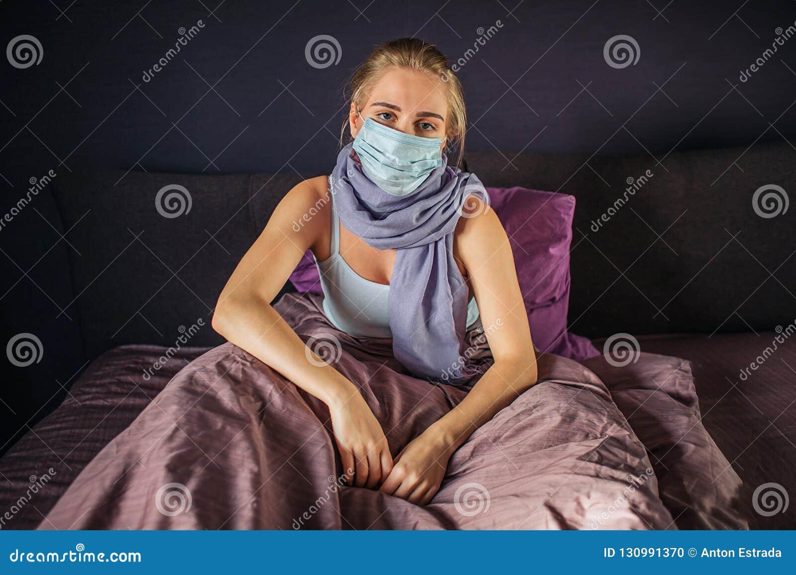 De stille en ernstige besmette jonge vrouw zit op bed en kijkt op camera Zij is omvat met deken De jonge vrouw heeft