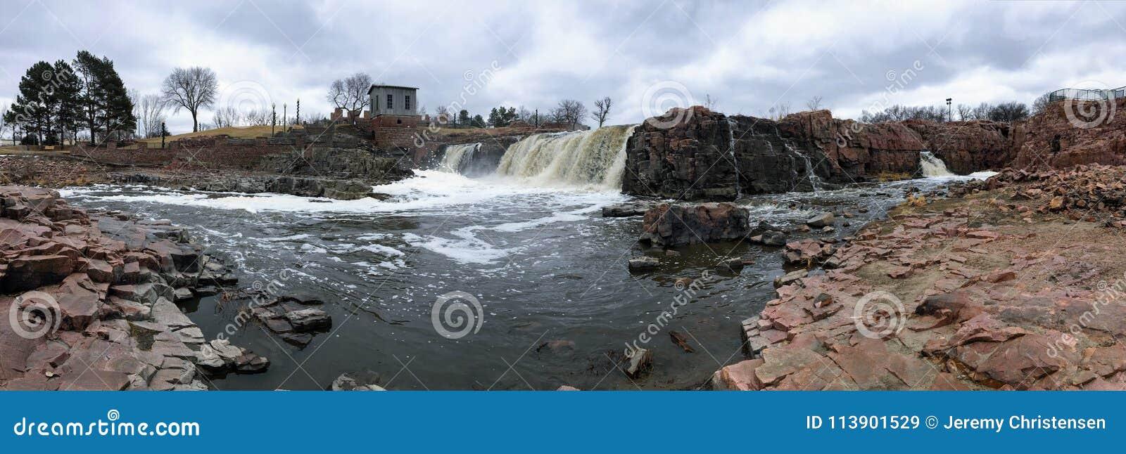 De stora Sioux River flödena över vaggar i Sioux Falls South Dakota med sikter av djurliv, fördärvar, parkerar banor, drevspårbro