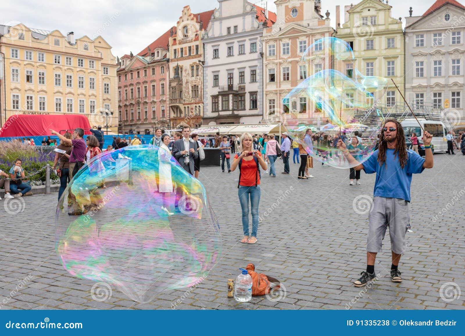 De straatentertainer creeert grote bellen door zeepachtig water te gebruiken en een kabel en de mensen hebben ter beschikking pre