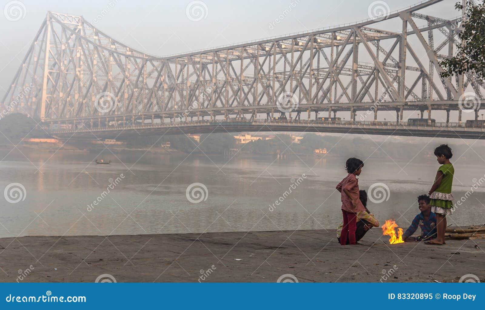 De straatjonge geitjes houden op een koude mistige de winterochtend warm in Mallick ghat dichtbij de brug van Howrah bij de bank