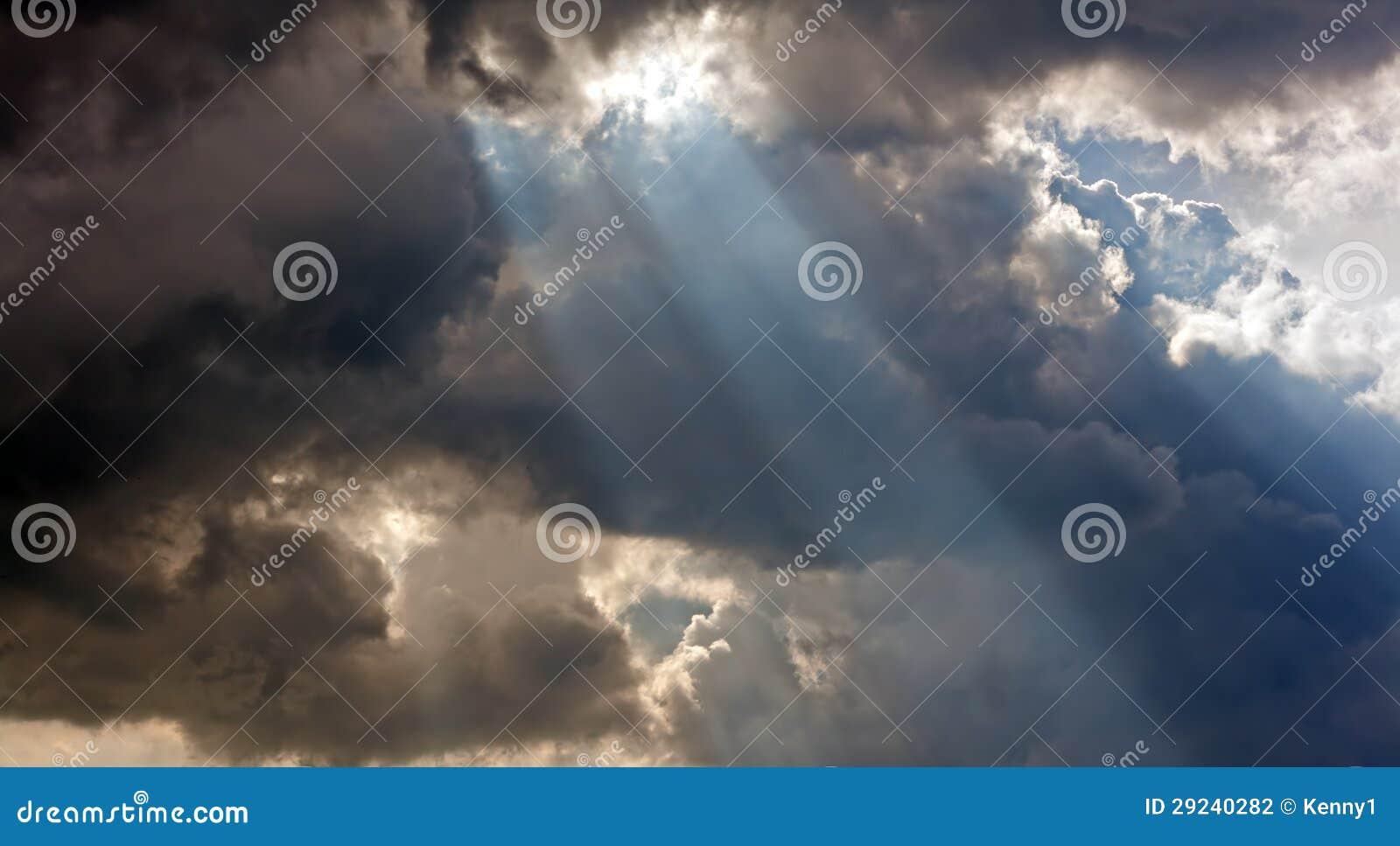 De stralen van de zon door onweerswolken