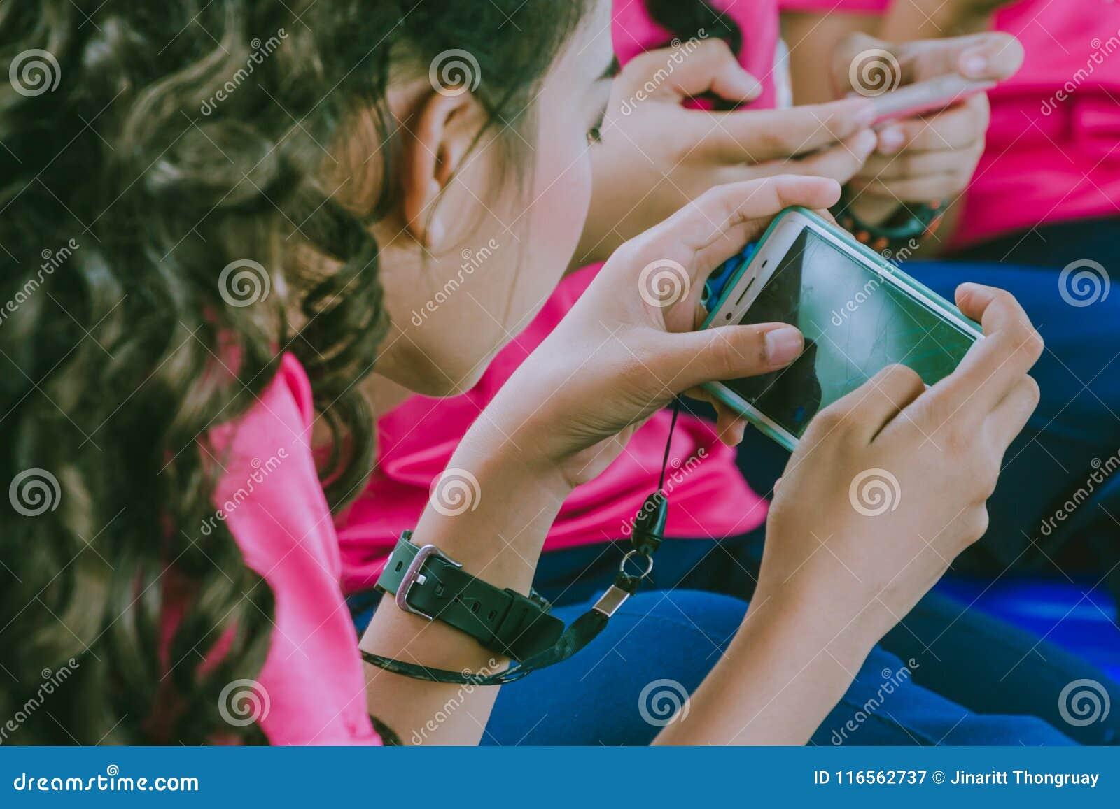 De studenten spelen spelen met mobiele telefoons