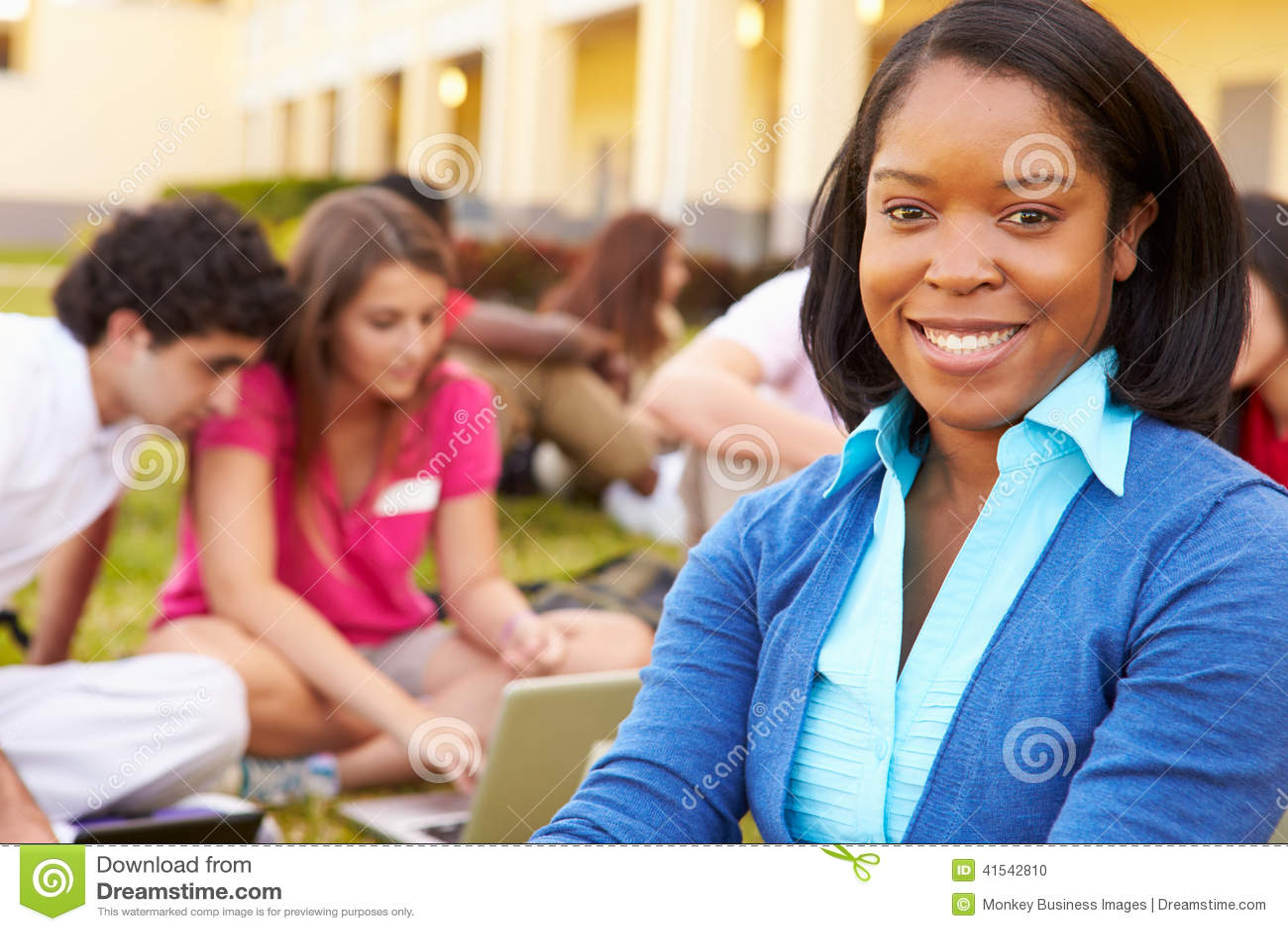 De Studenten van Sitting Outdoors With van de middelbare schoolleraar op Campus
