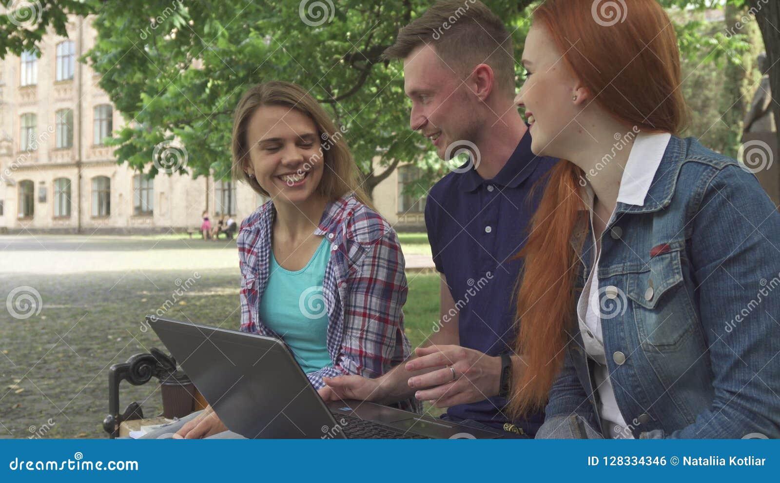 De studenten werken aan laptop op campus