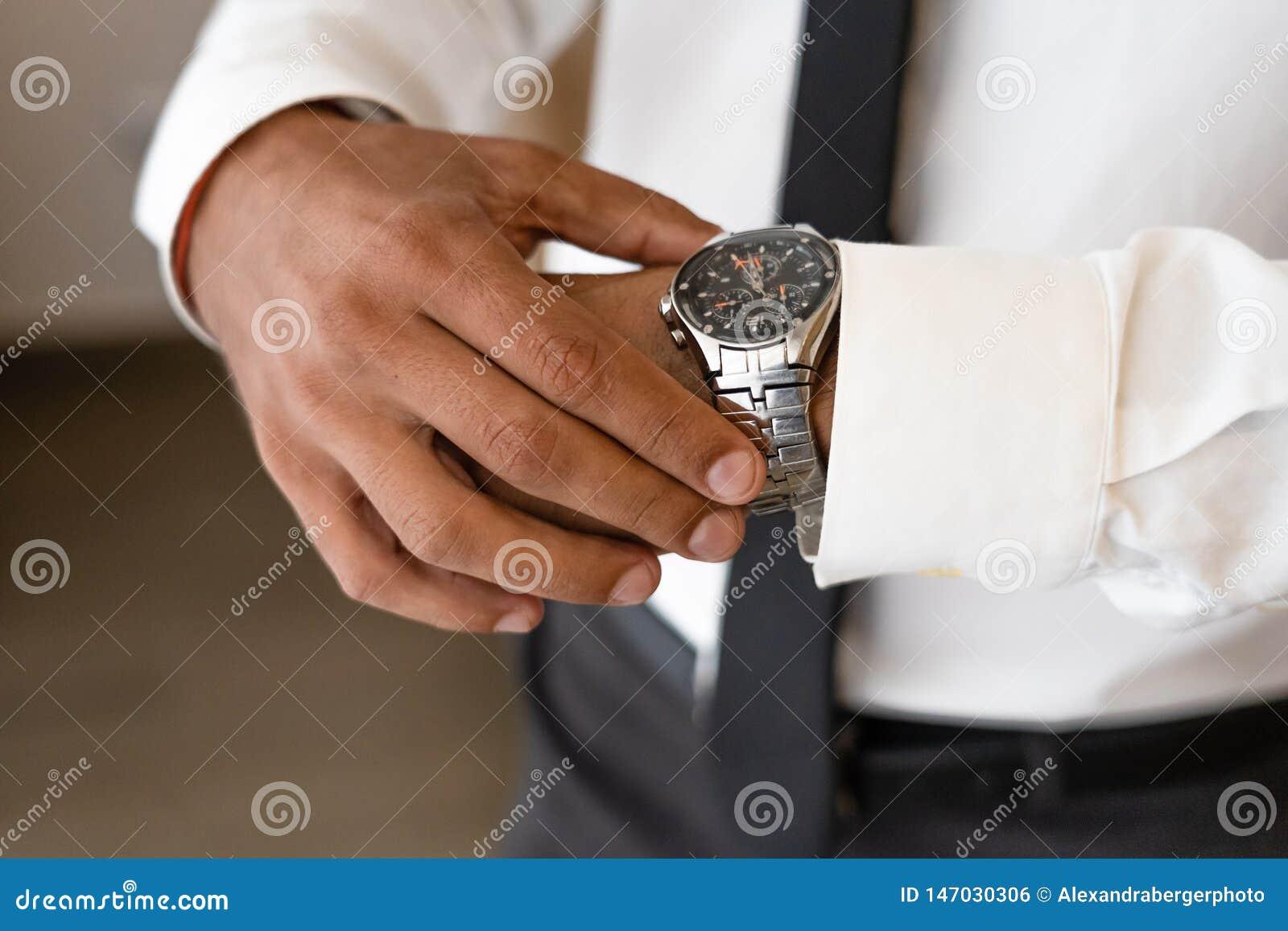 De succesvolle mens met witte overhemd en stropdas kijkt op horloge
