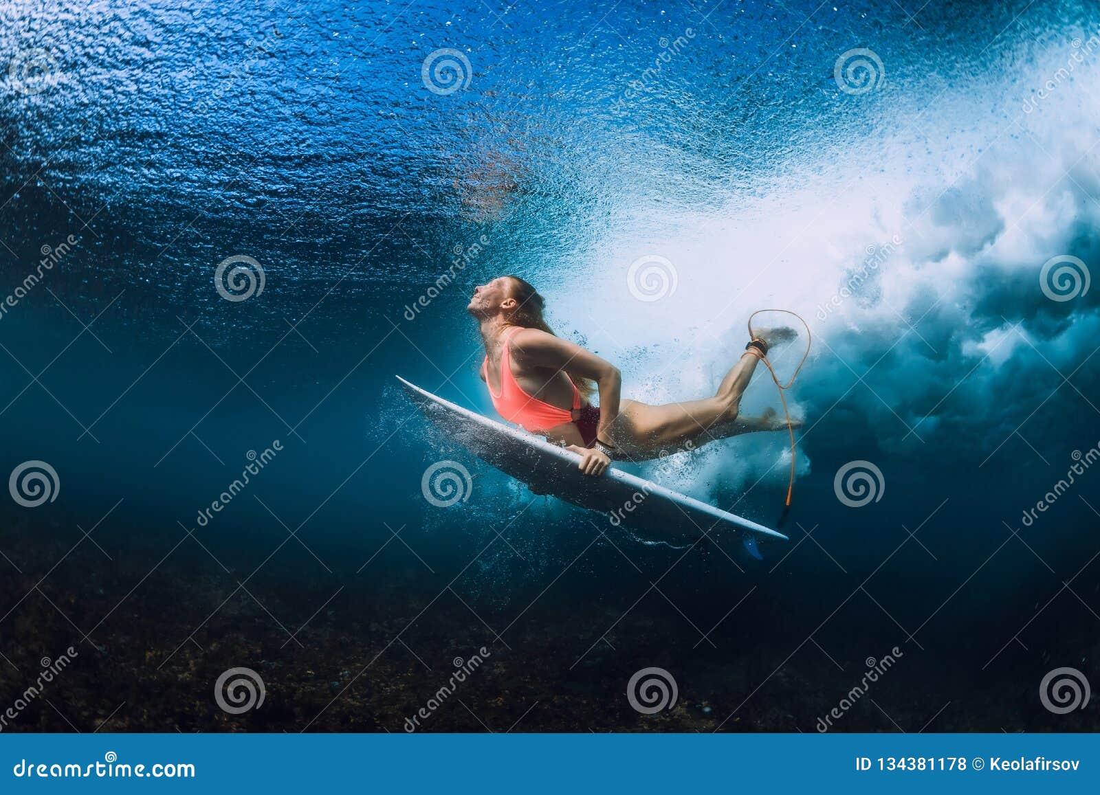 De surfervrouw met surfplank duikt onderwater
