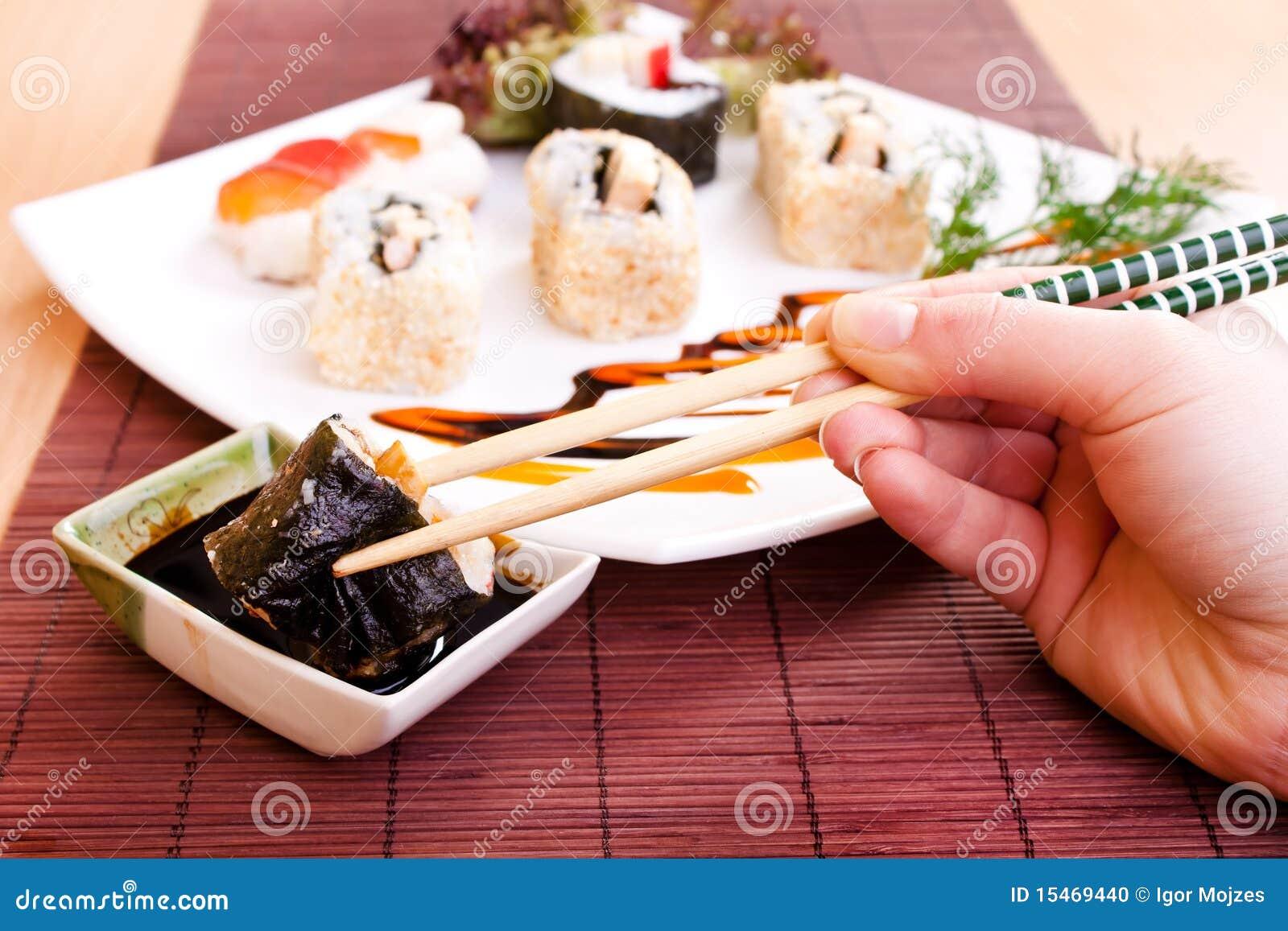 De sushibroodje van de holding met eetstokjes