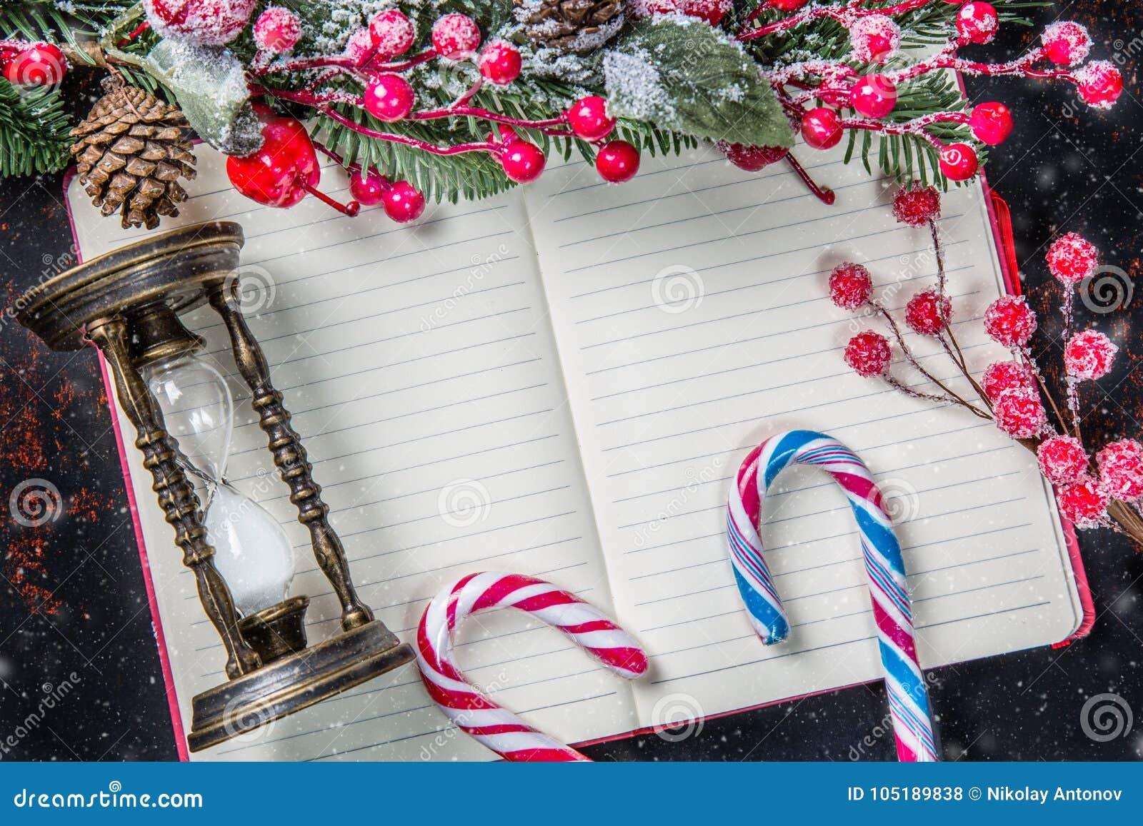 De takken van de Kerstmisspar, decoratie, suikergoedriet, bevroren rode bessen, kegel en uitstekend zandloperkader op notitieboek