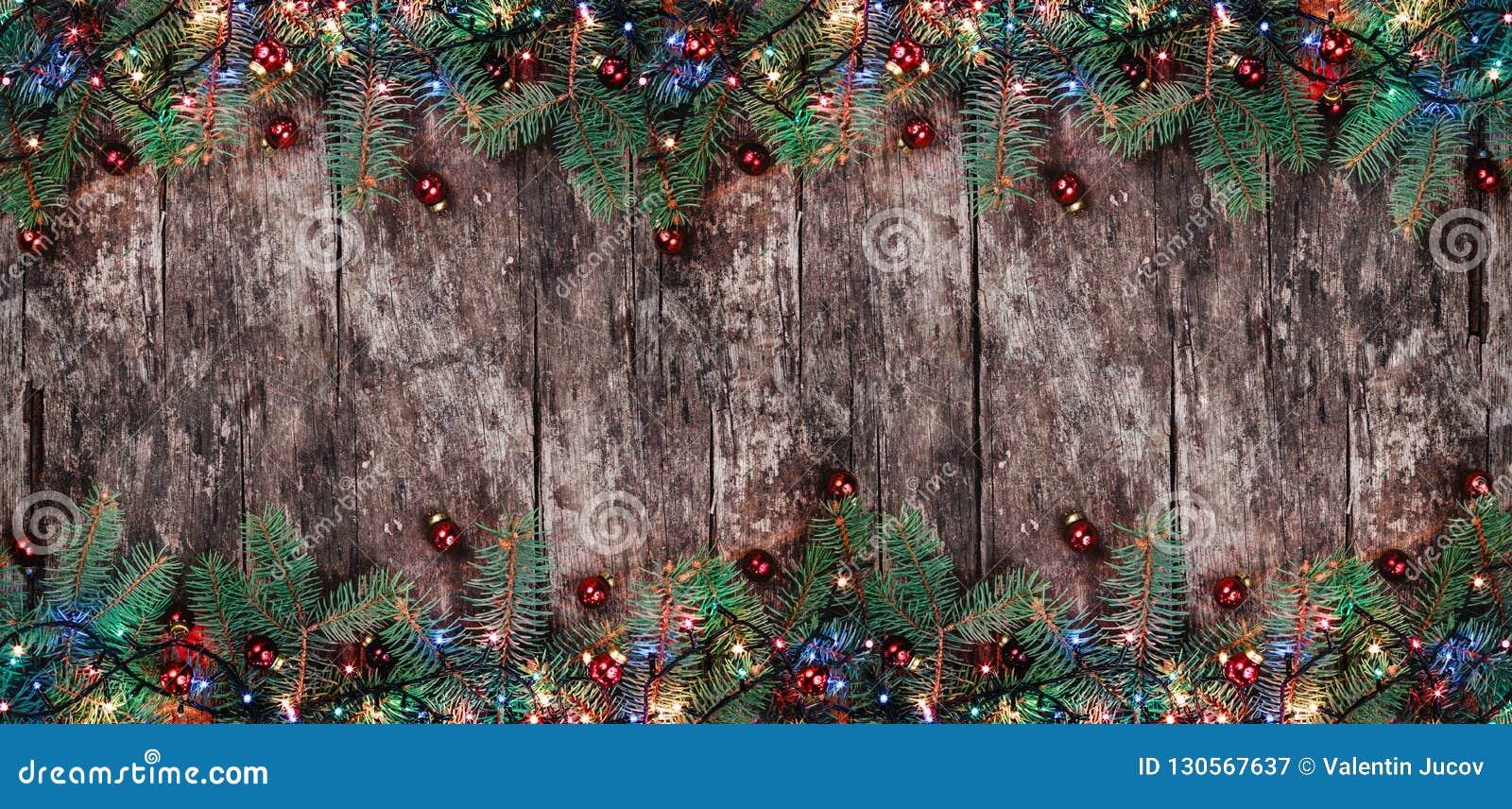 De takken van de Kerstmisspar met lichten en rode decoratie op houten achtergrond Kerstmis en Gelukkige Nieuwjaarsamenstelling